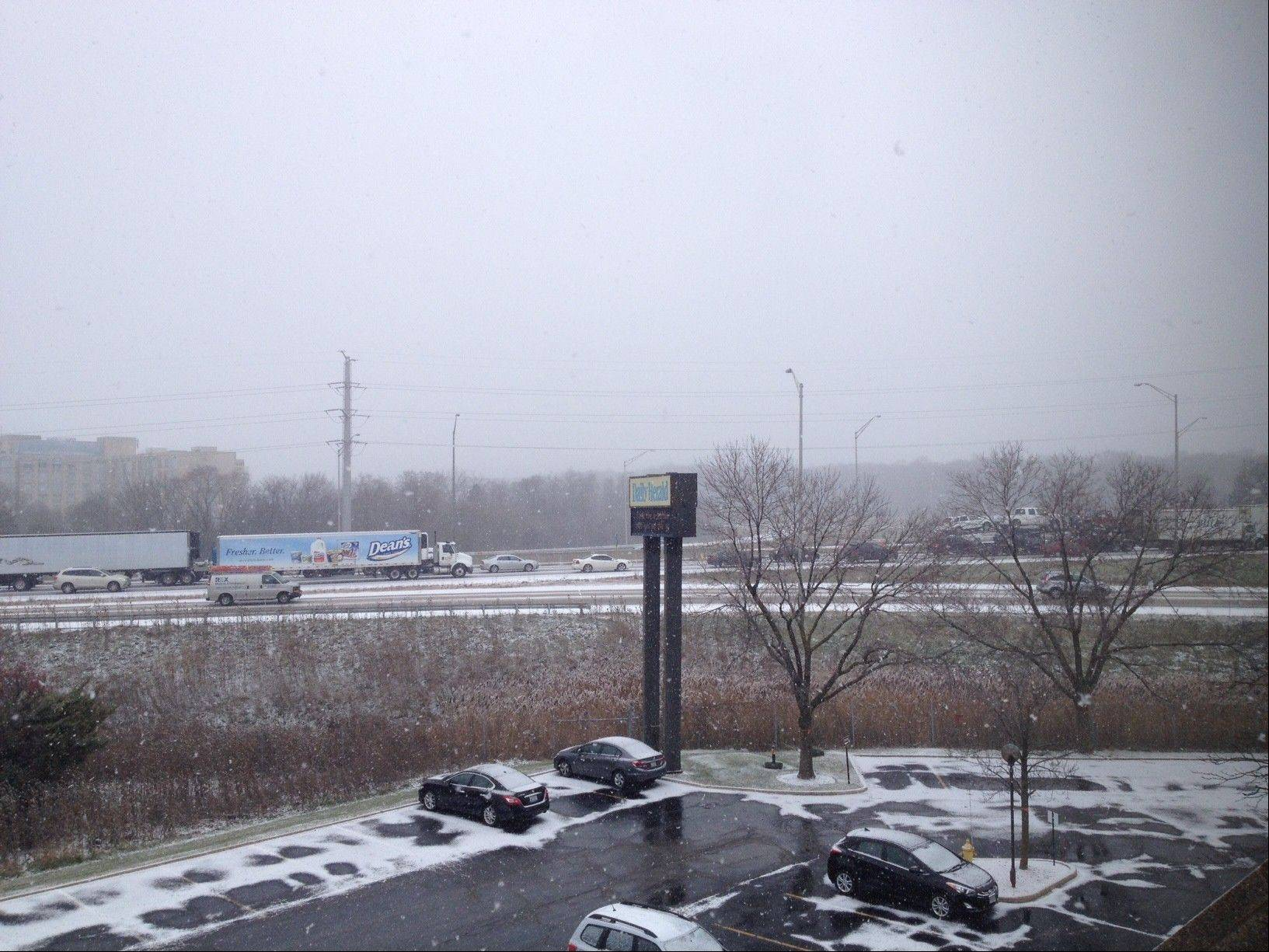 Snow is falling in the Northwest suburbs, causing traffic to back up on I-90 near Arlington Heights.