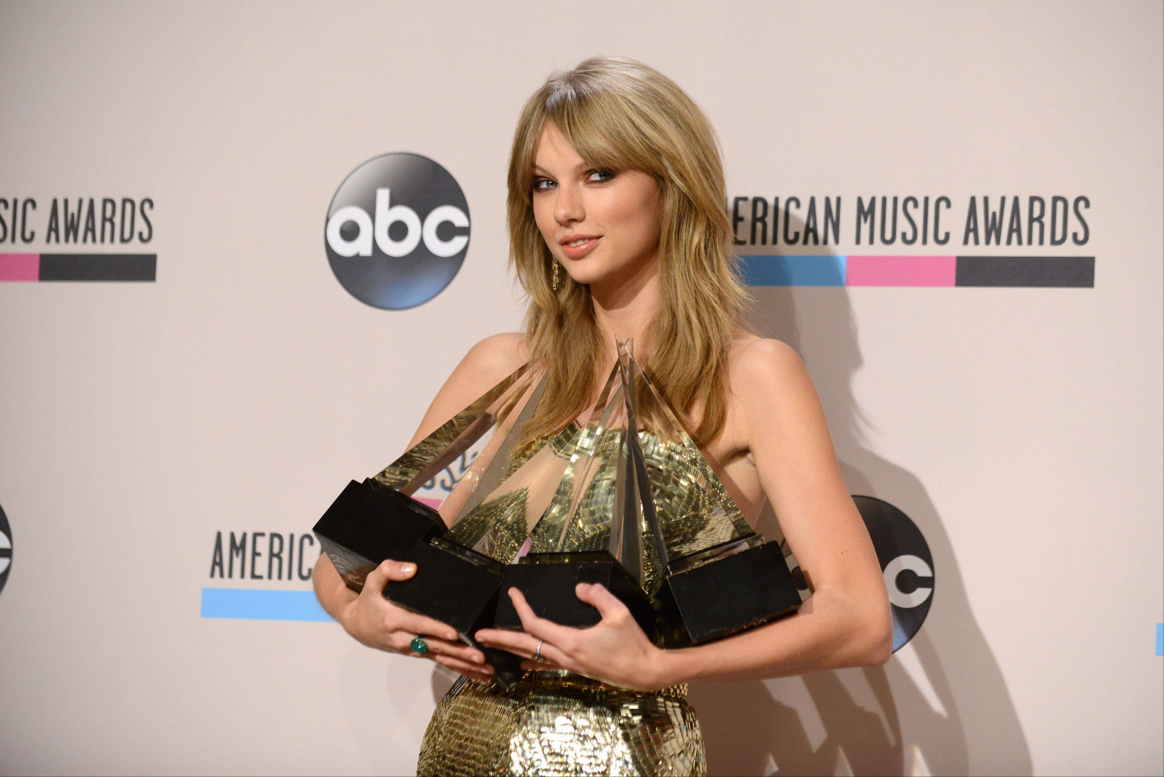 "Taylor Swift poses backstage with the awards for favorite album — country for ""Red,"" favorite female artist — pop/rock, favorite female artist — country, and artist of the year at the American Music Awards at the Nokia Theatre L.A. Live on Sunday in Los Angeles."