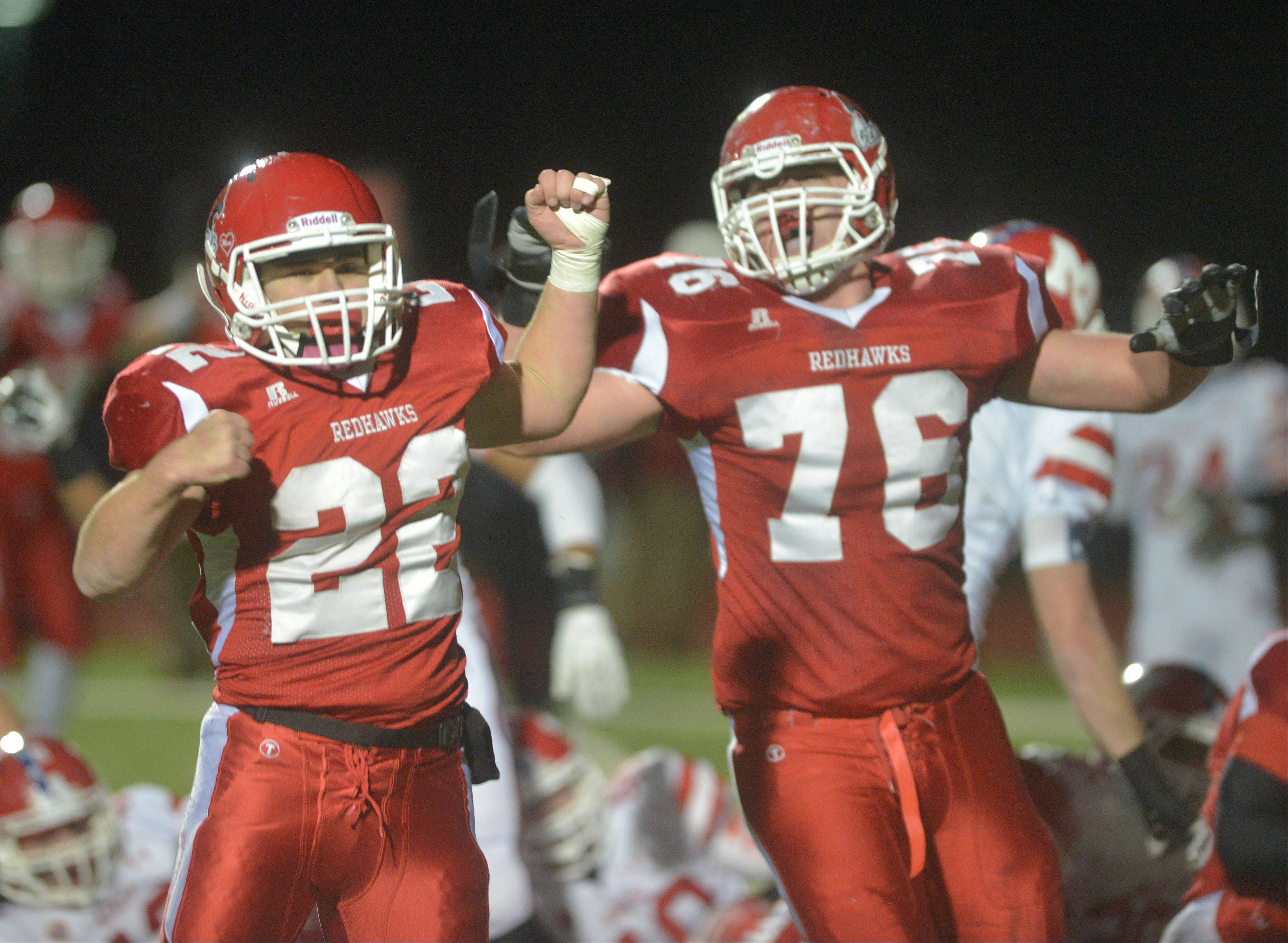 Kevin Clifford, left, and Ryan Minick of Naperville Central celebrate the game-winning touchdown against Marist Saturday night in the Class 8A semifinals. The Redhawks' 27-21 win advanced the team to the state championship game against Loyola Academy at 7 p.m. on Saturday, Nov. 30 at Huskie stadium in DeKalb.