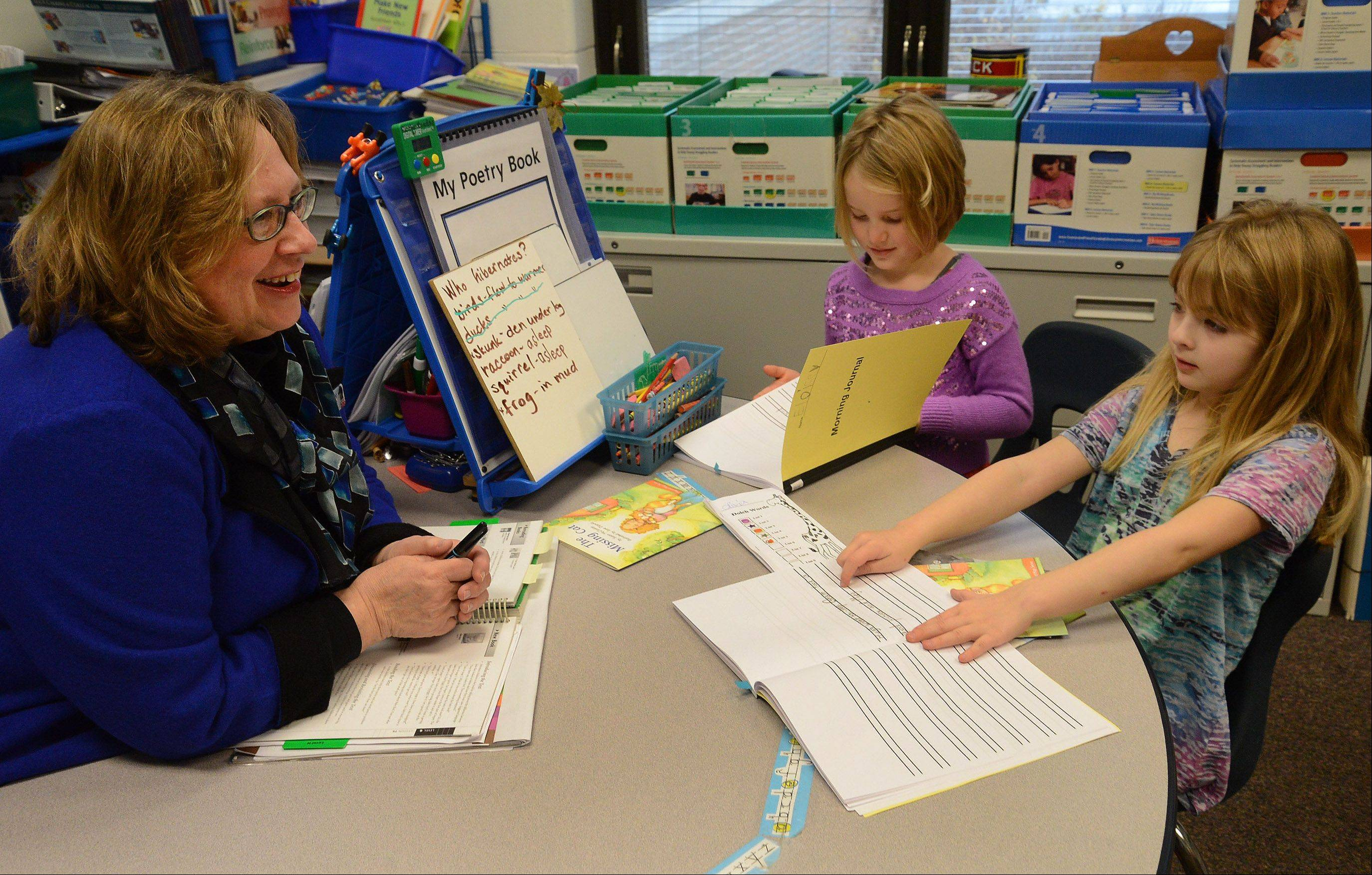 Reading Specialist Sylvia Chidley works with students Eloise Nelson, left, and Olivia Martelon at Roslyn Road Elementary School in Barrington. The school is one of three from Northwest Cook County to win a National Blue Ribbon Award this year.