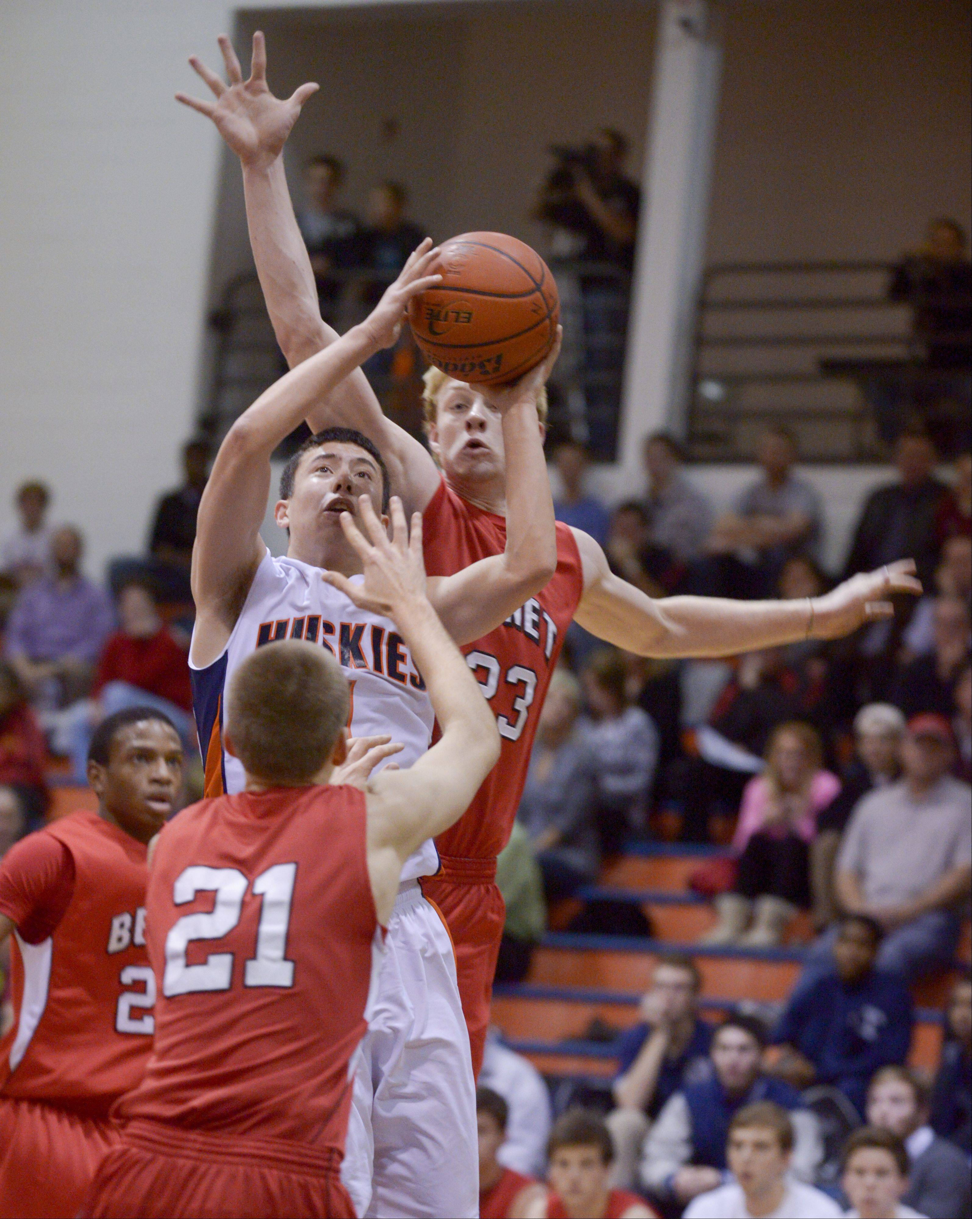 Naperville North's Jayson Winick works to take a shot past Benet's Daniel Roemer during in boys basketball in Naperville Sunday.