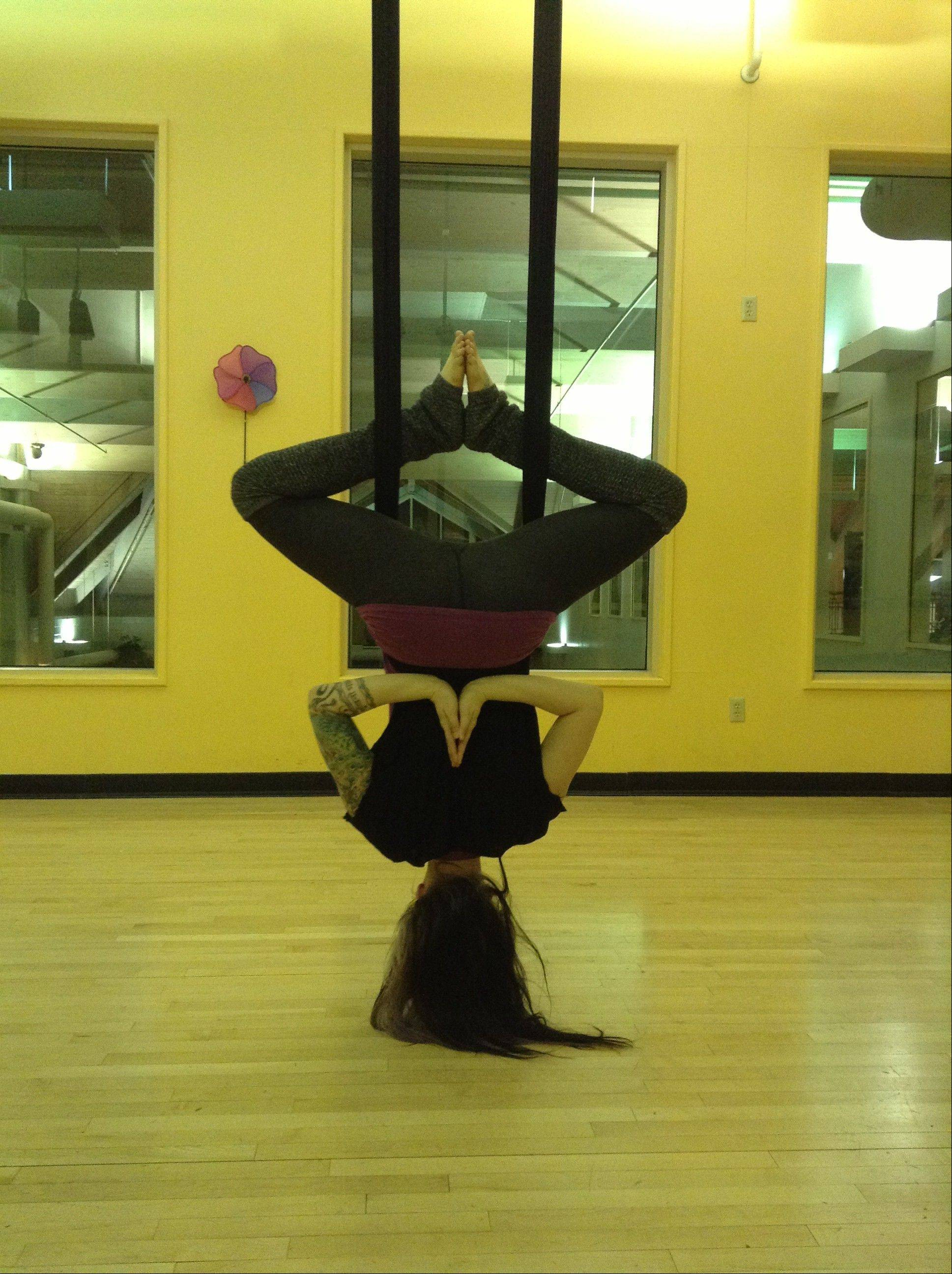 Teacher Sarah Starnes of Naperville flips upside-down one of the aerial yoga poses.