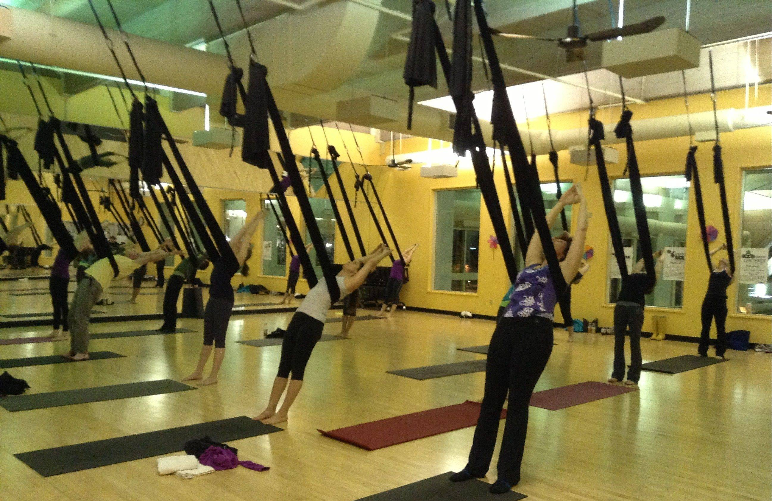 Students at Sky Fitness in Buffalo Grove lean back onto the black silks during an aerial yoga class. The silks provide different support and traction than a regular yoga class on a mat.