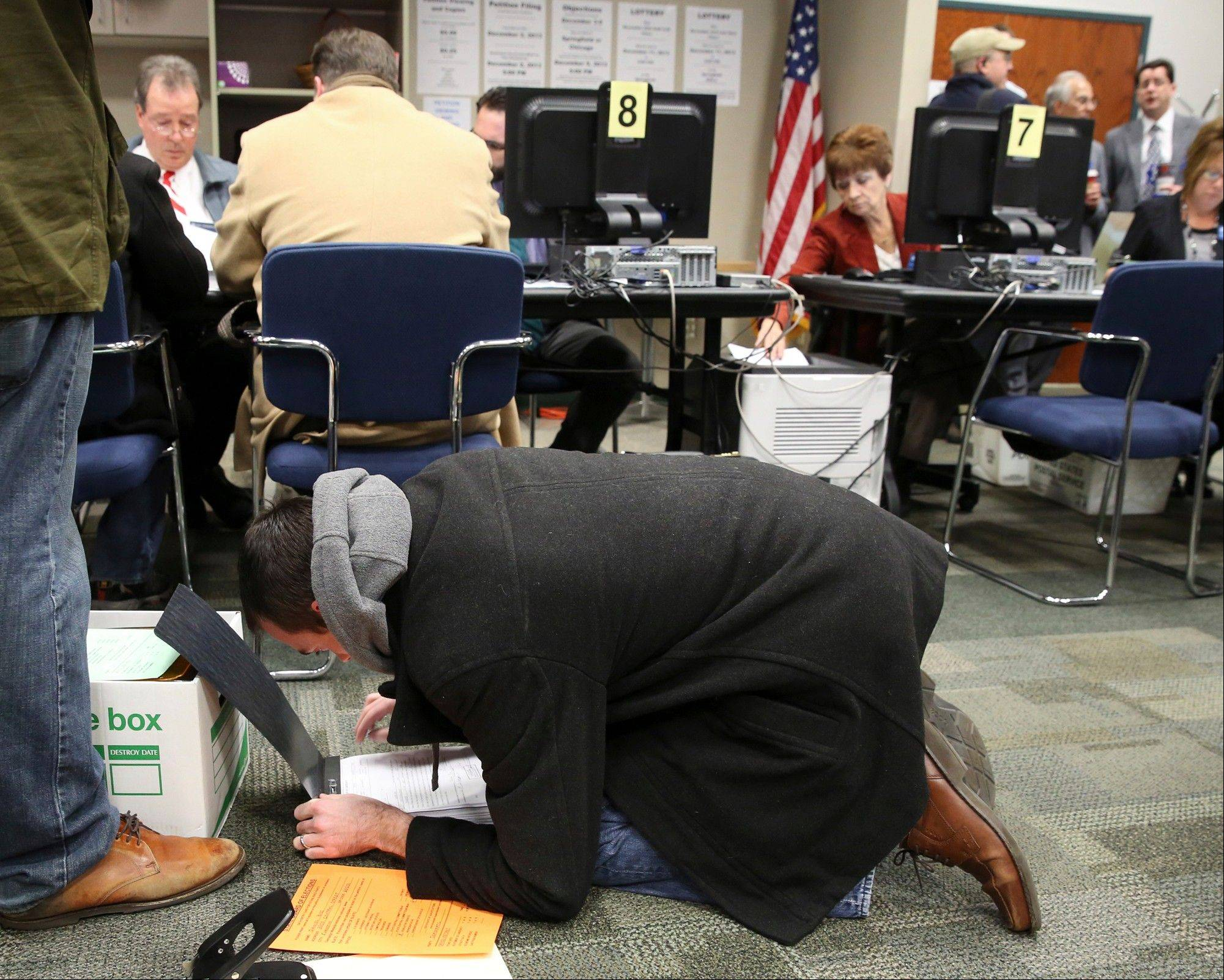 Jake Butcher attaches paperwork to petitions he filed on behalf of Illinois Senate Democratic candidates Monday at the Illinois State Board of Elections office in Springfield.