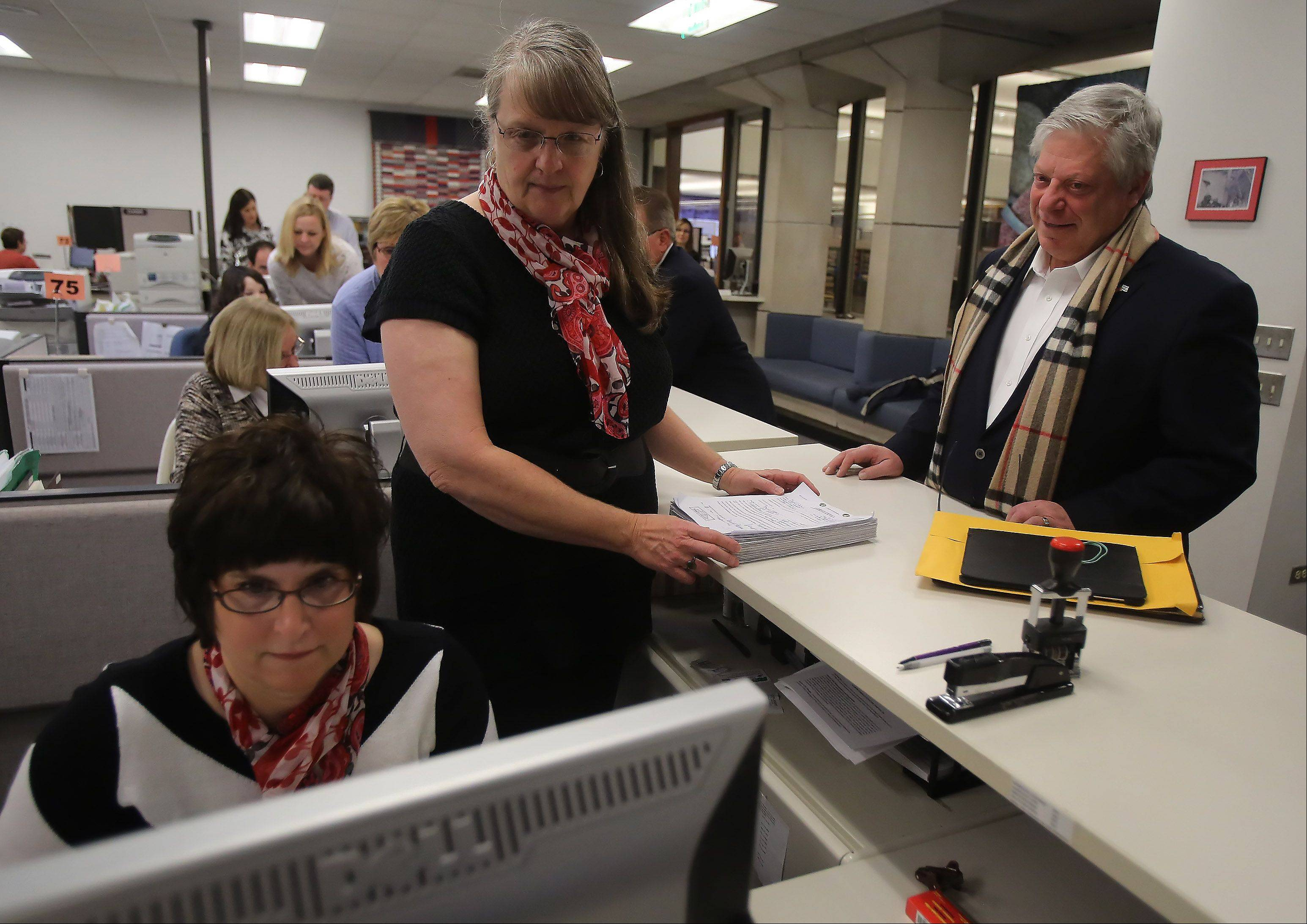 Lake County treasurer candidate David Stolman works with Lake County clerk's staffers MaryAnn Potter and Laura Huelsmann to file his paperwork Monday.