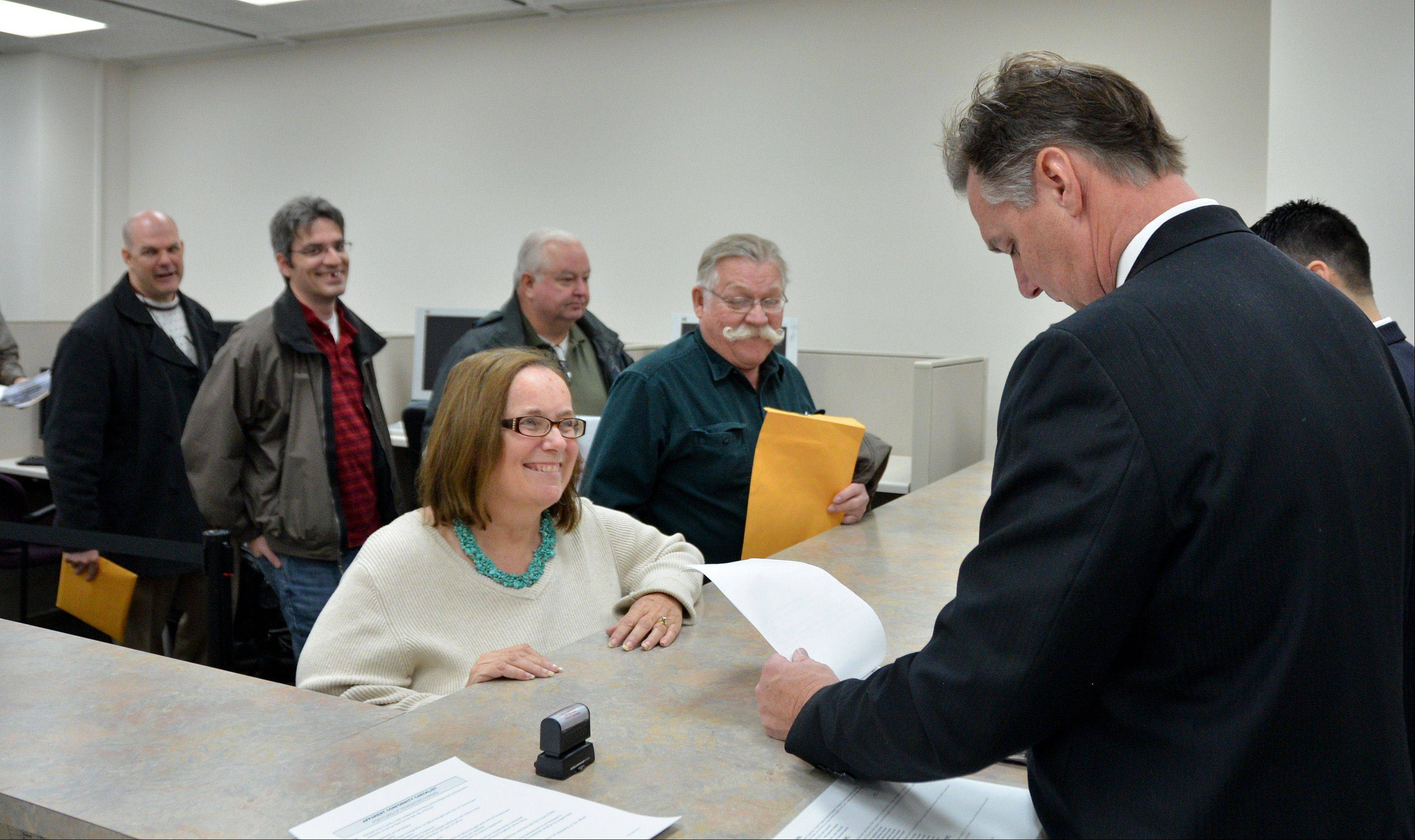 "DuPage County Board hopeful Paula McGowen of Glen Ellyn, center, arrived at 5:15 a.m. Monday to be the first person in line to file for the March 18 primary election. A self-described ""early bird,"" she arrived 45 minutes before the doors opened at 6 a.m. even though she couldn't file until 8 a.m."
