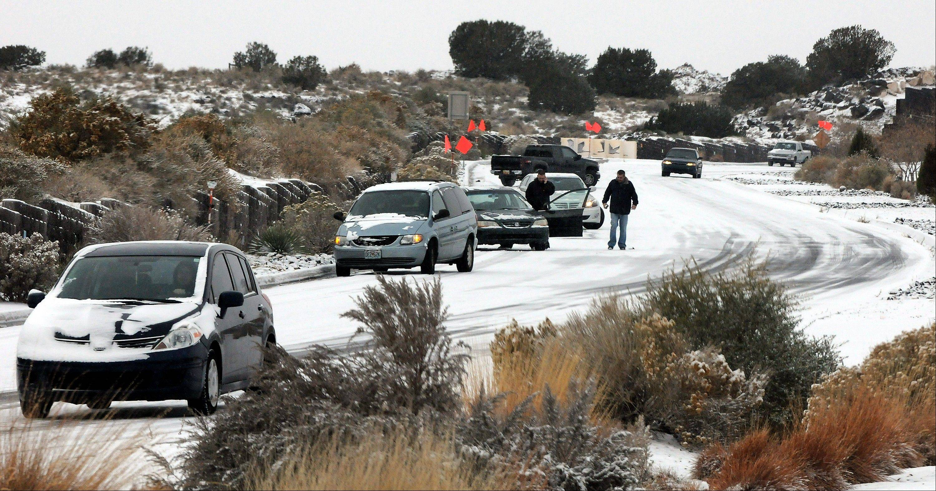 Cars slide on Paseo del Norte Sunday in Albuquerque, N.M., after a winter storm hit New Mexico over the weekend. A large storm already blamed for at least eight deaths in the West slogged through Oklahoma, Texas, New Mexico and other parts of the southwest Sunday as it slowly churned east ahead of Thanksgiving.