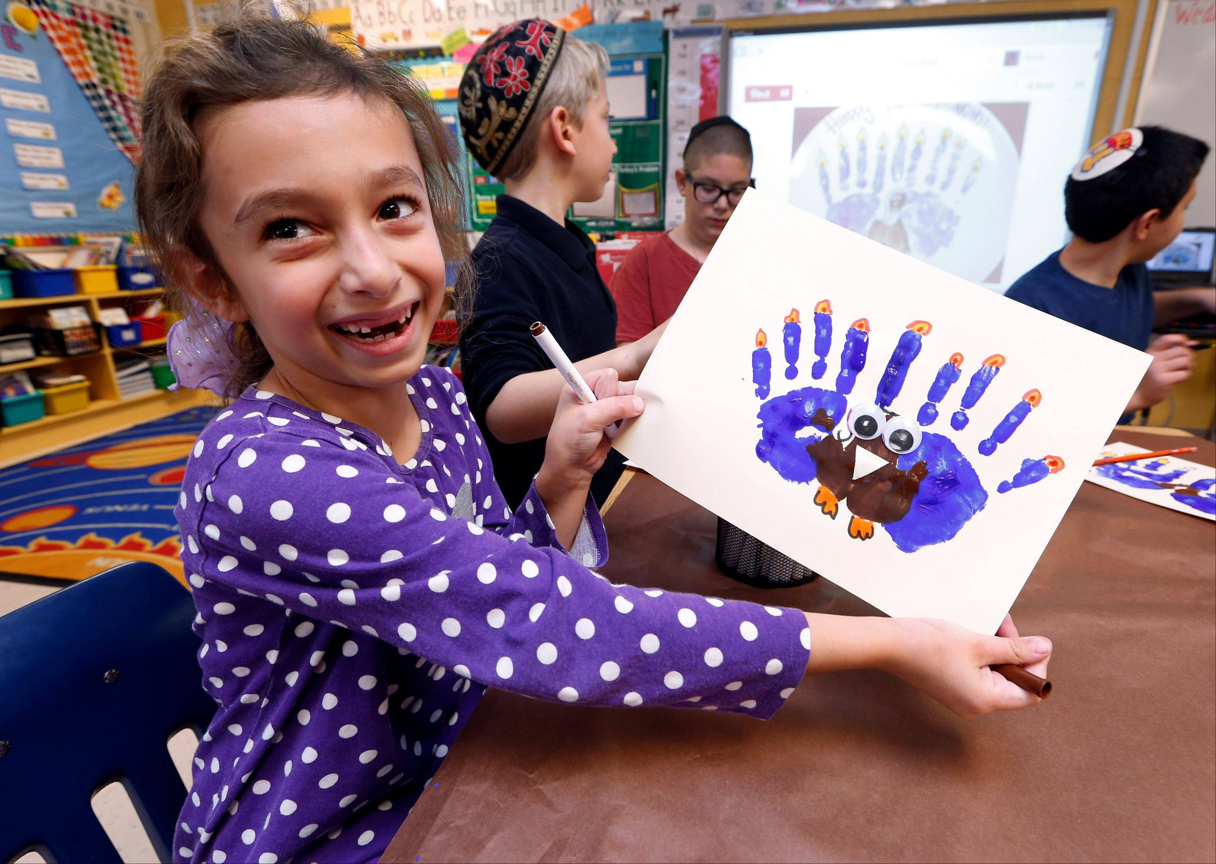 Second-grader Rozie Aronov, 7, holds up a menurkey, a paper-and-paint mashup of a menorah and turkey, she created at Hillel Day School in Farmington Hills, Mich. The recent class project reflects one way for Jews in the United States to deal with a rare quirk of the calendar that overlaps Thanksgiving with the start of Hanukkah. The last time it happened was 1888 and the next time is 79,043 years from now � by one estimate that �s widely repeated in Jewish circles.