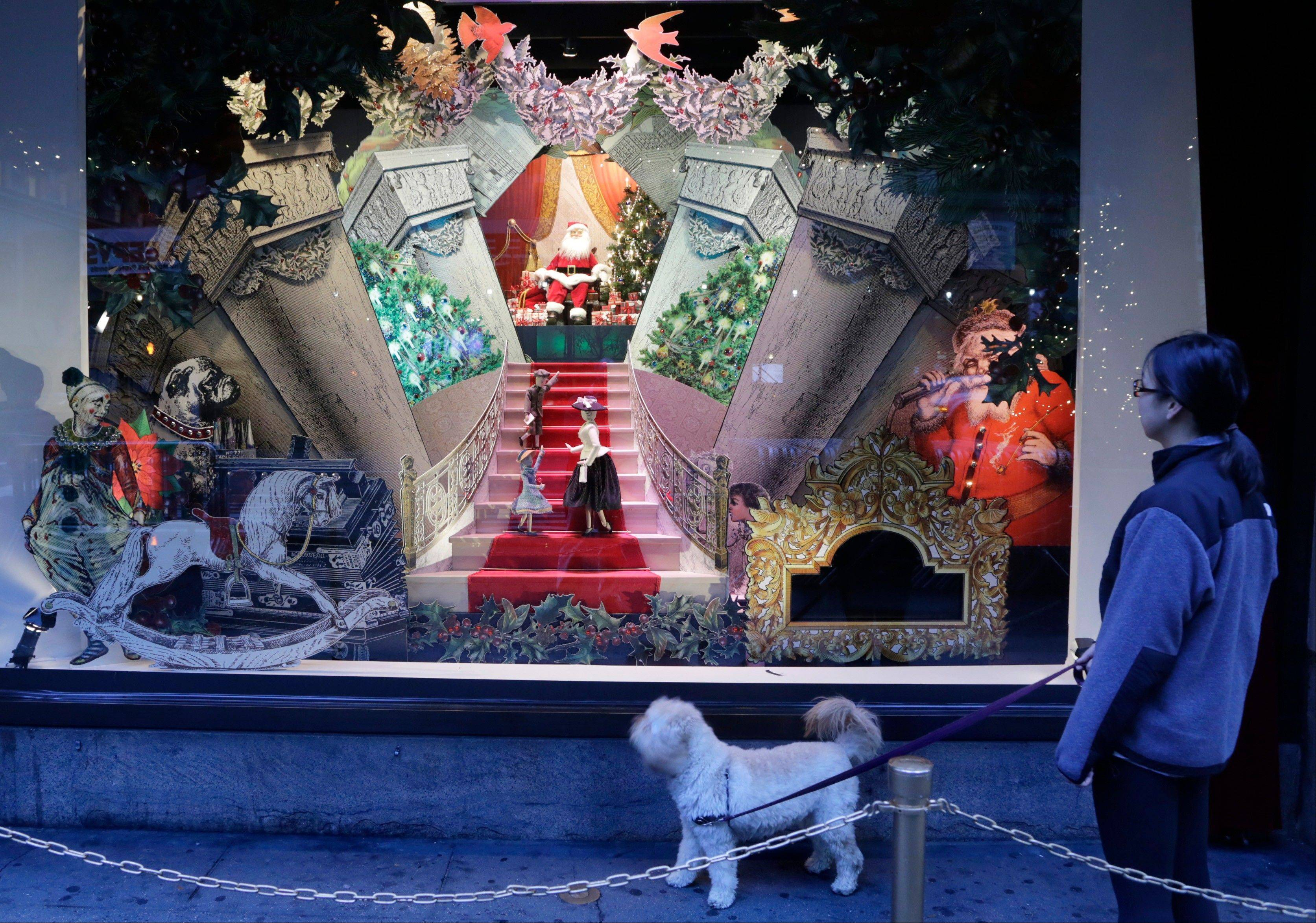 A woman walks her dog past a vintage Santa Claus holiday window display at Lord & Taylor department store in New York. Forget window shopping, some of Manhattan�s biggest and most storied retailers say their elaborate seasonal window displays are a gift to passers-by.