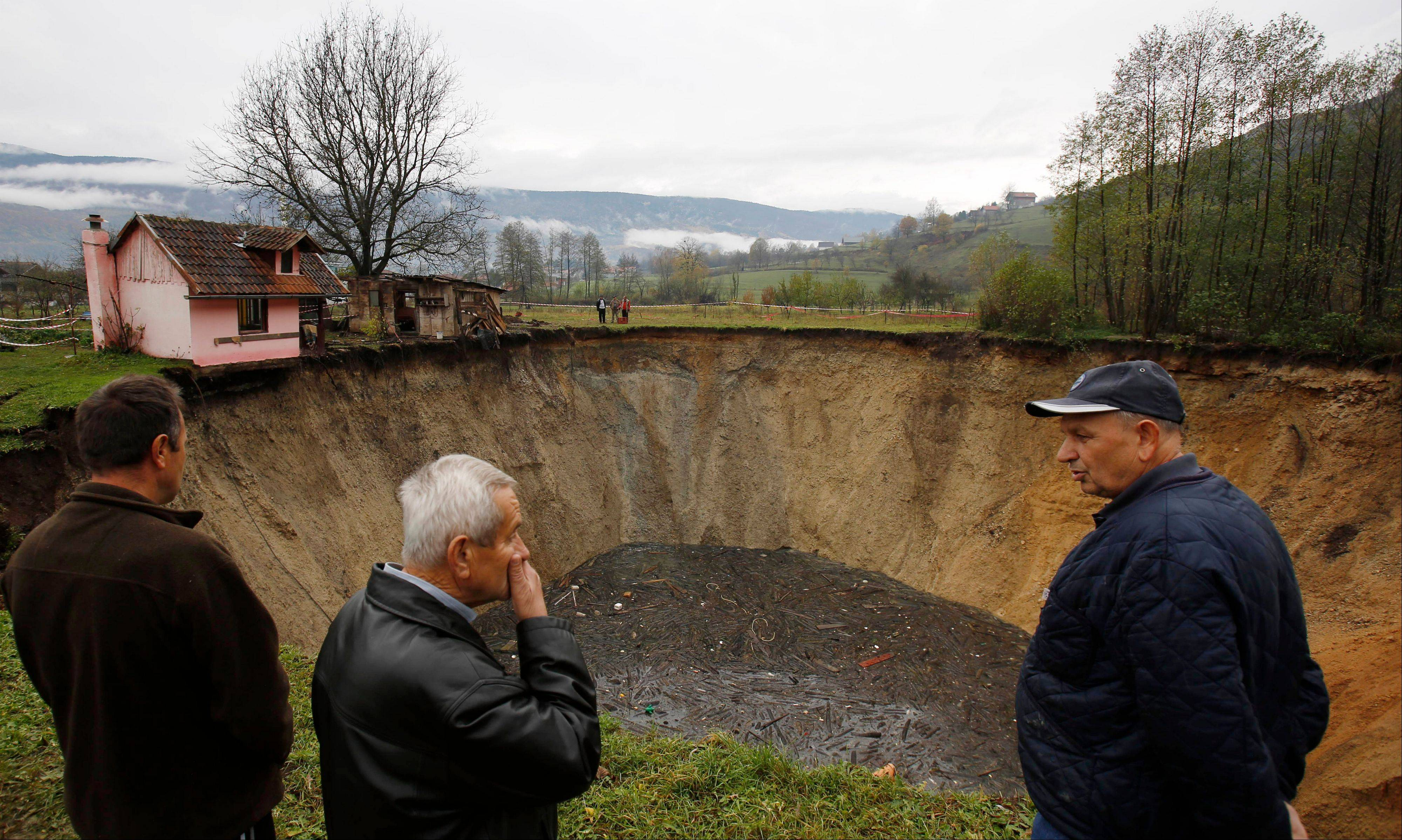 People gather around a huge sinkhole in the village of Sanica, Bosnia. Only weeks ago, the spot was a pond full of fish and floating green algae, lined with old willow and plum trees, and a grass field where cattle used to peacefully graze.