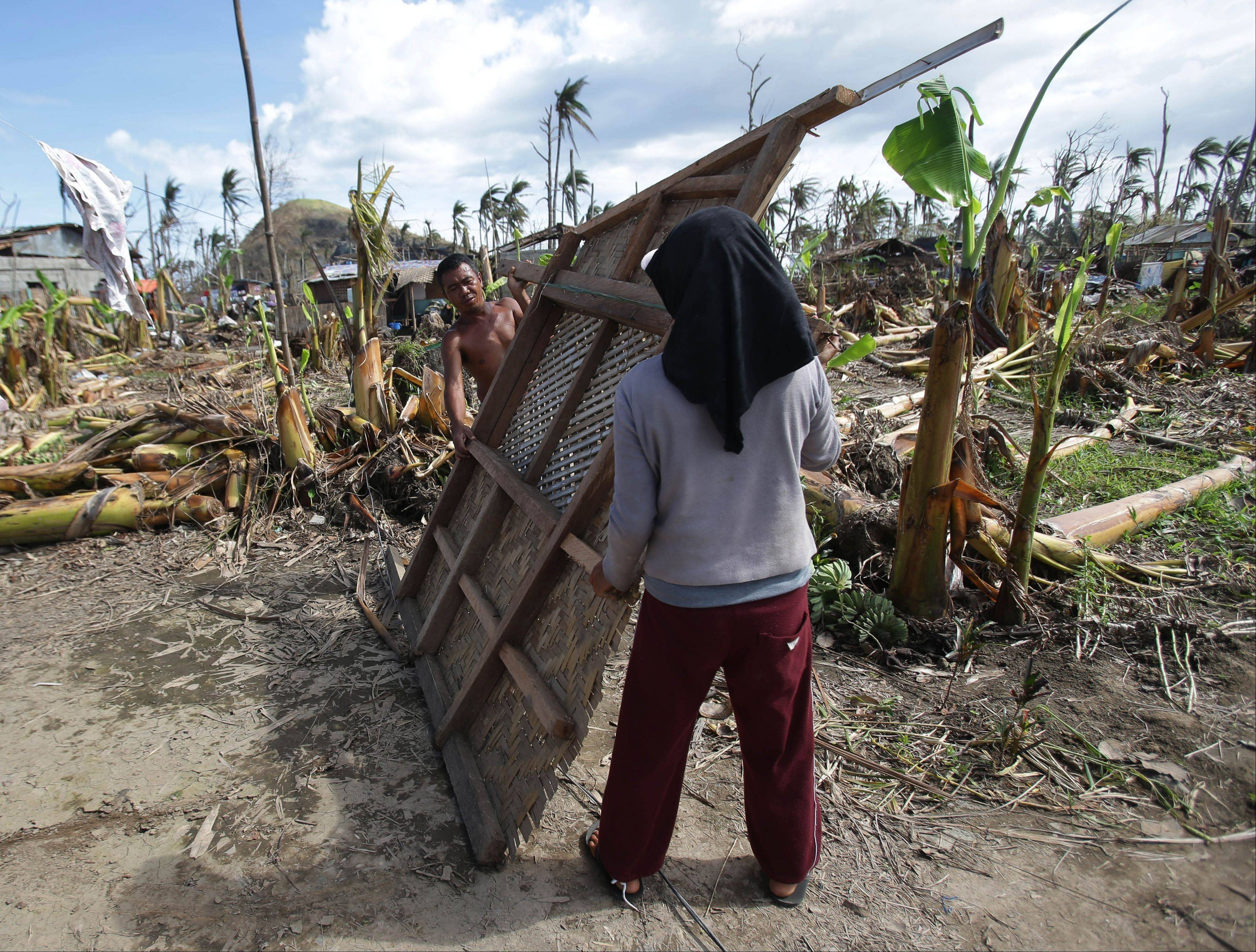 Coconut farmer Mario Duma, left, tries to rebuild his house in Tanuan, Leyte, central Philippines.