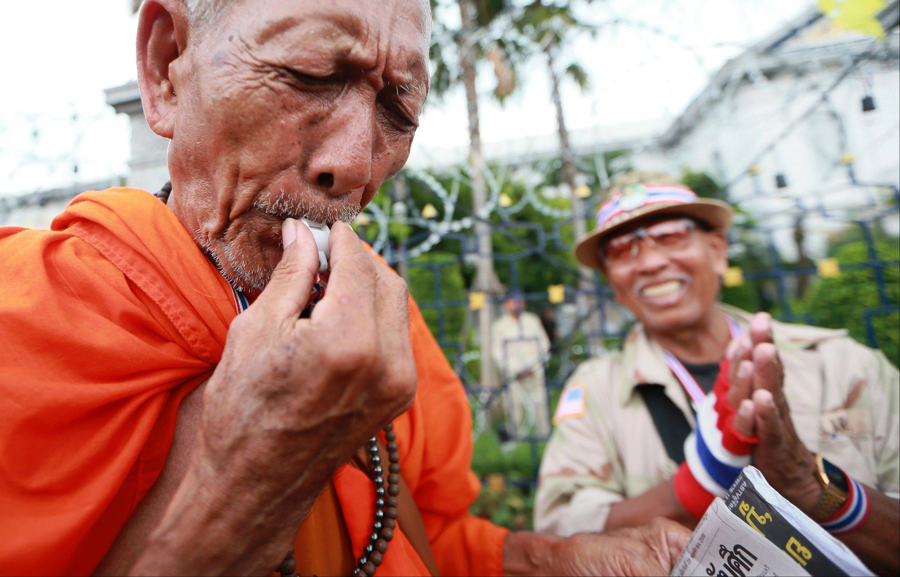 A Thai Buddhist monk blows a whistle during a rally outside Interior Ministry in Bangkok, Thailand, Tuesday, Nov. 26, 2013. Protesters forced the closure of several government ministries Tuesday and vowed to take control of state offices nationwide in a bid to oust Prime Minister Yingluck Shinawatra, escalating the biggest challenge she has faced since taking office.