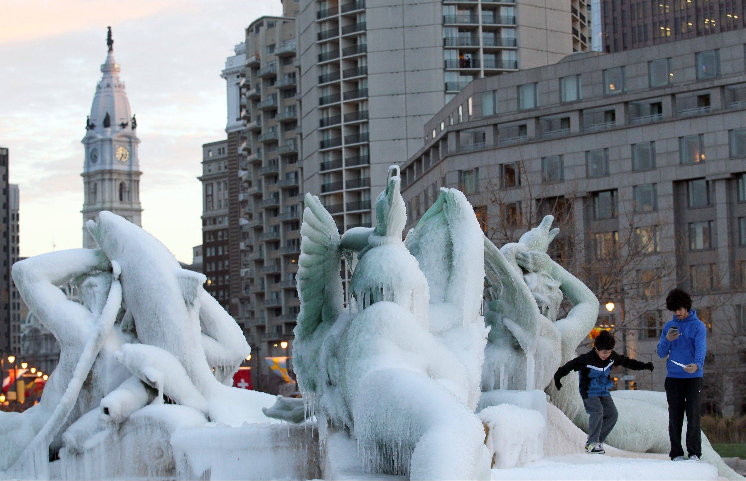 Faisal Almuohen, left, and Abduliz Almuohen play in the frozen Swann Memorial Fountain at Logan Circle, Monday, Nov. 25, 2013, in Philadelphia.