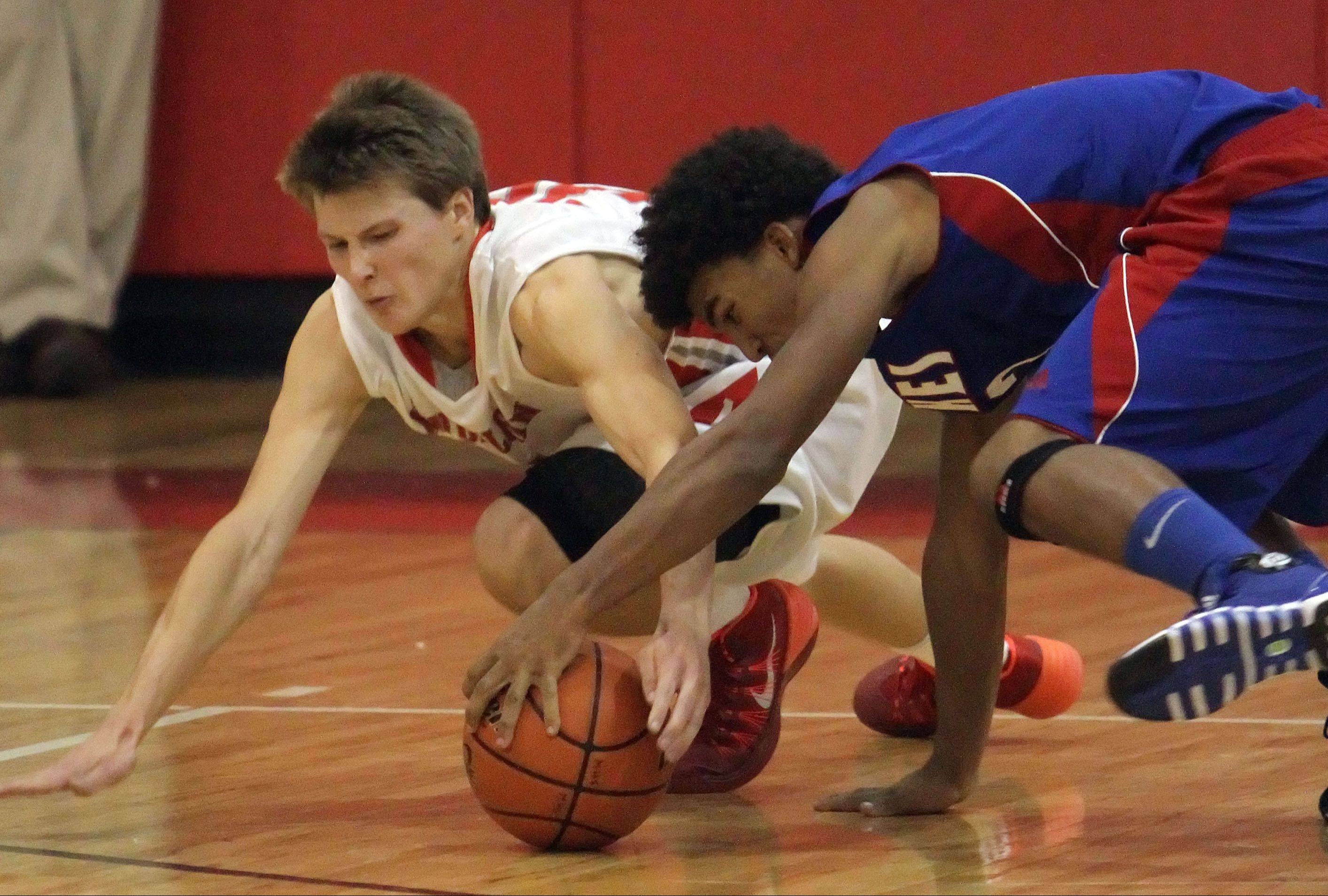 Mundelein�s J.T Michalski, left, Lakes� Devyn Cedzidlo scramble for a loose ball Tuesday at Mundelein.