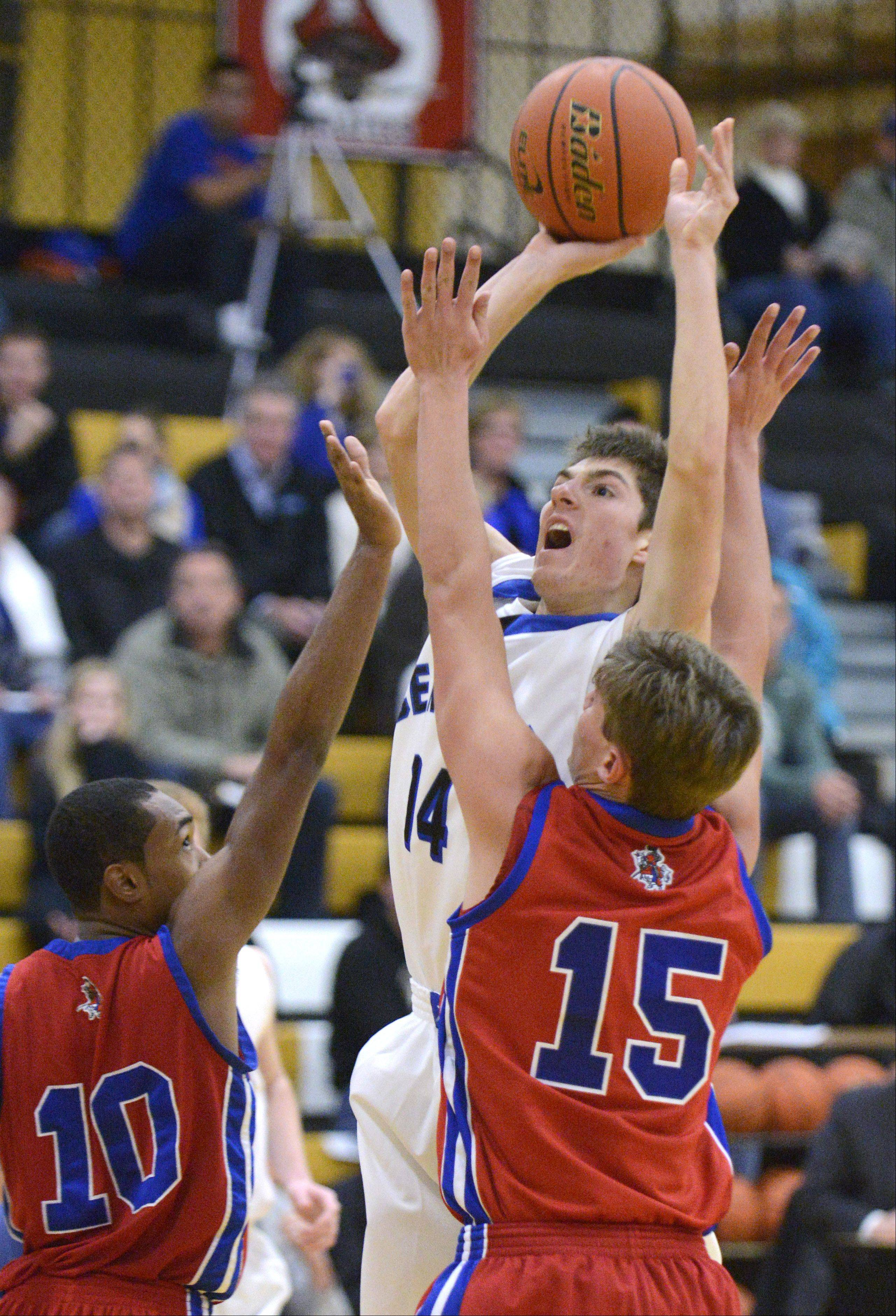 Burlington Central�s Jacob Schutta sinks a shot over a block by Dundee-Crown�s Kiwaun Seals (10) and Nick Munson in the third quarter on Tuesday at Sycamore.