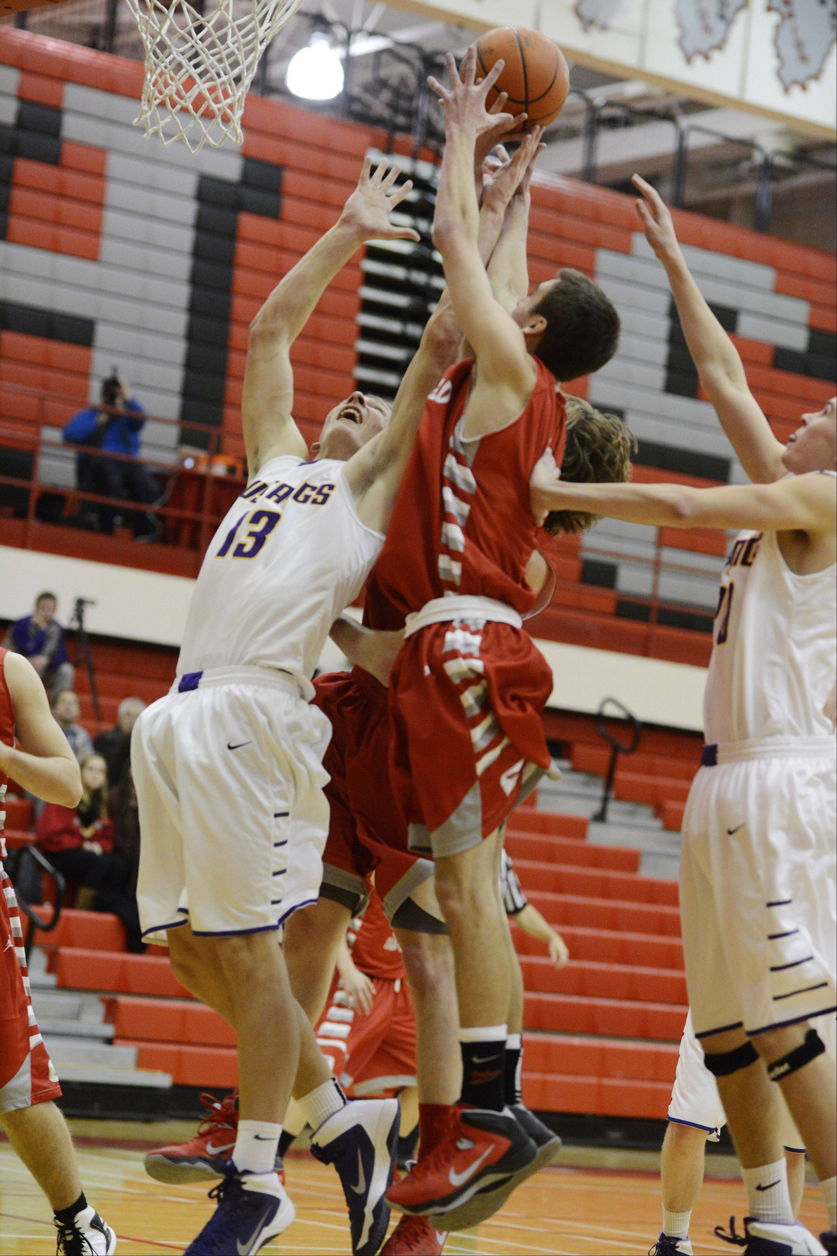 Rolling Meadows� Matt Dolan, left, and Pat Kramp, right, leap for a rebound against Deerfield�s Jack Gurvey during Tuesday�s game in Palatine.