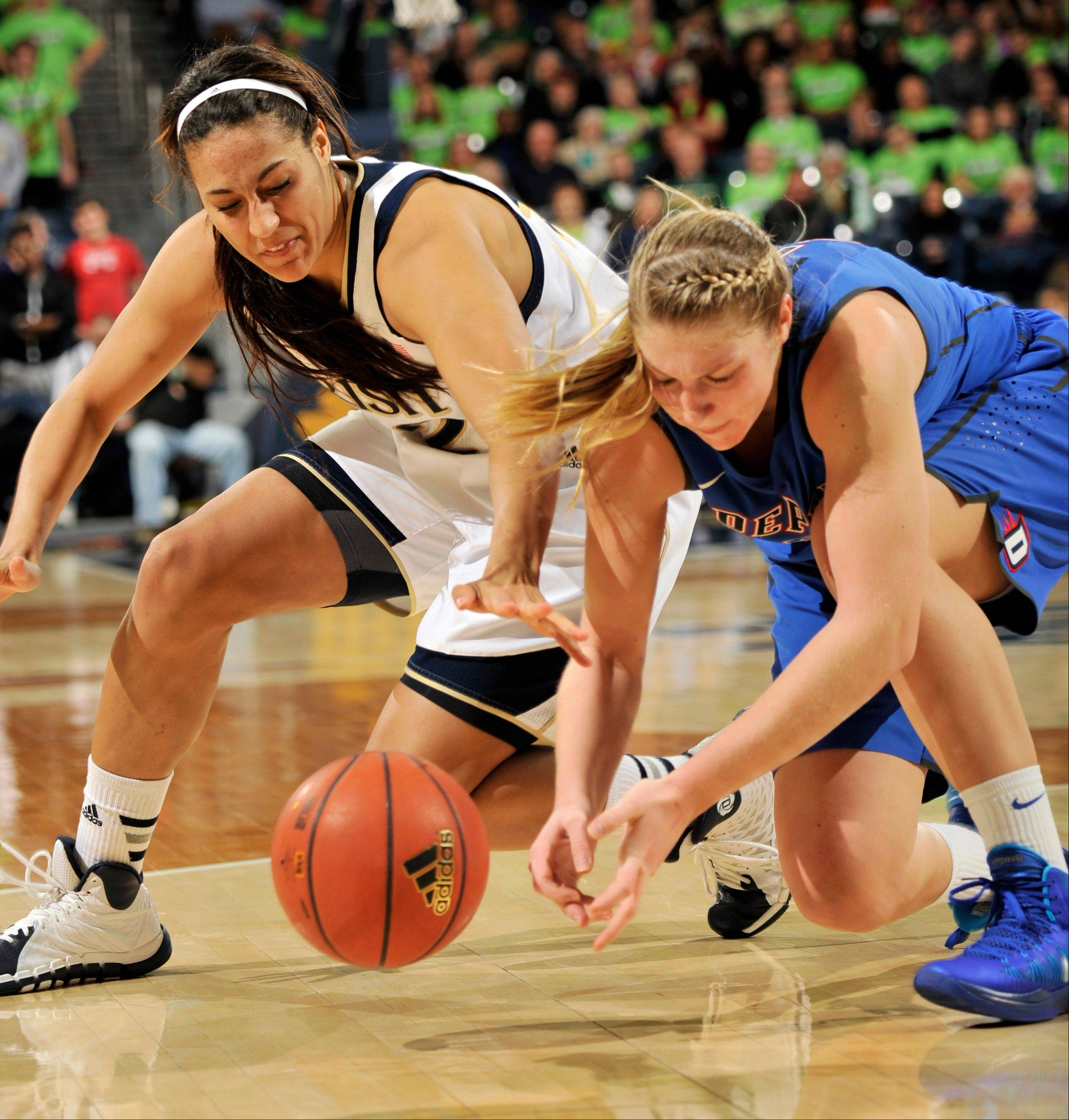 Notre Dame forward Taya Reimer, left, and DePaul guard Megan Podkowa battle for a loose ball during the second half of an NCAA college basketball game, Tuesday, Nov. 26, 2013, in South Bend, Ind. Notre Dame won 92-76. (AP Photo/Joe Raymond)
