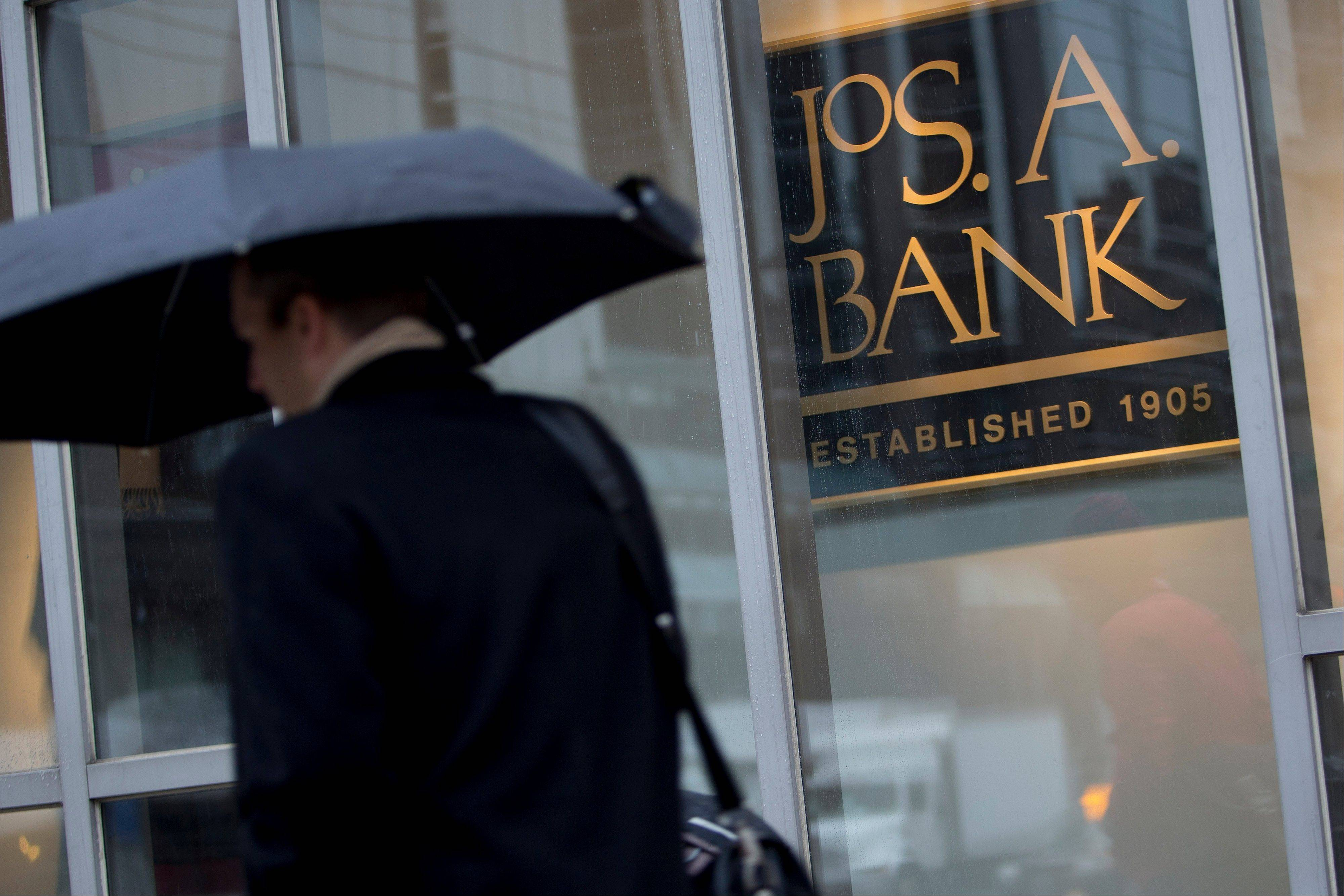 A pedestrian carrying an umbrella walks past a Jos. A. Bank Clothiers Inc. store in Washington, D.C., U.S., on Tuesday, Nov. 26, 2013. Men's Wearhouse Inc., which less than two weeks ago let a takeover bid from Jos. A. Bank Clothiers expire without entering discussions, today offered to buy its smaller rival for about $1.54 billion.