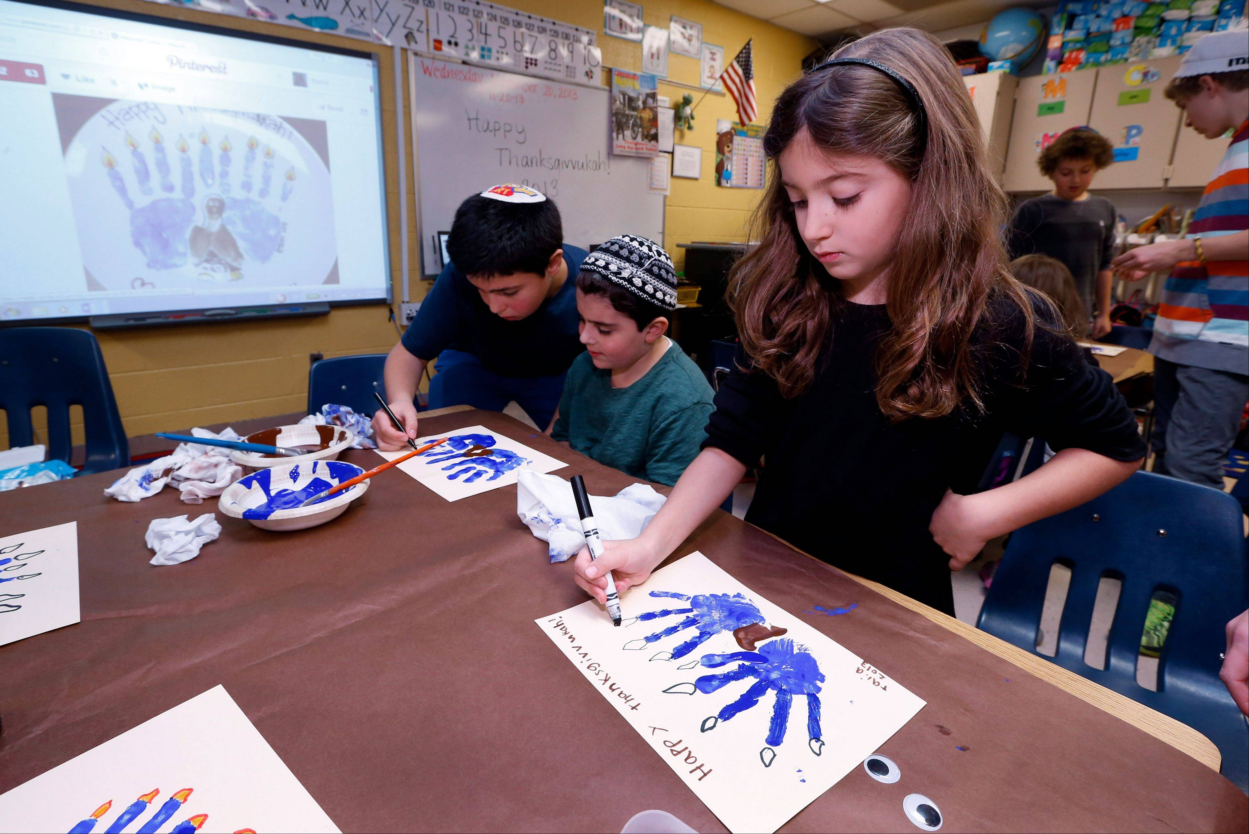Second-grader Talia Begres, 7, works on creating a menurkey, a paper-and-paint mashup of a menorah and turkey at Hillel Day School in Farmington Hills, Mich. The recent class project reflects one way for Jews in the United States to deal with a rare quirk of the calendar that overlaps Thanksgiving with the start of Hanukkah. The last time it happened was 1888 and the next time is 79,043 years from now -- by one estimate that �s widely repeated in Jewish circles.
