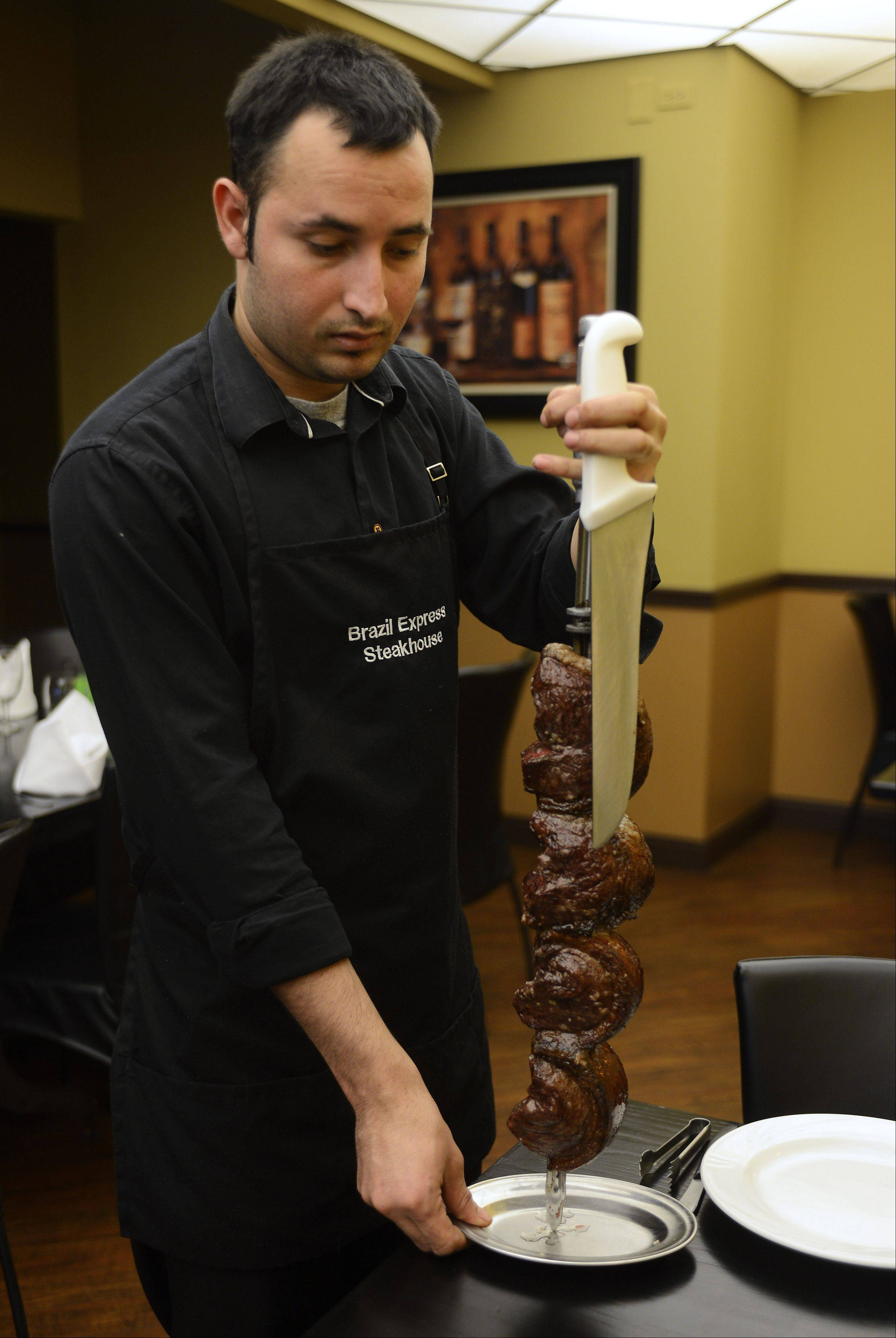 Mario Angueta shows off the piranha prime sirloin skewer at Brazil Express.