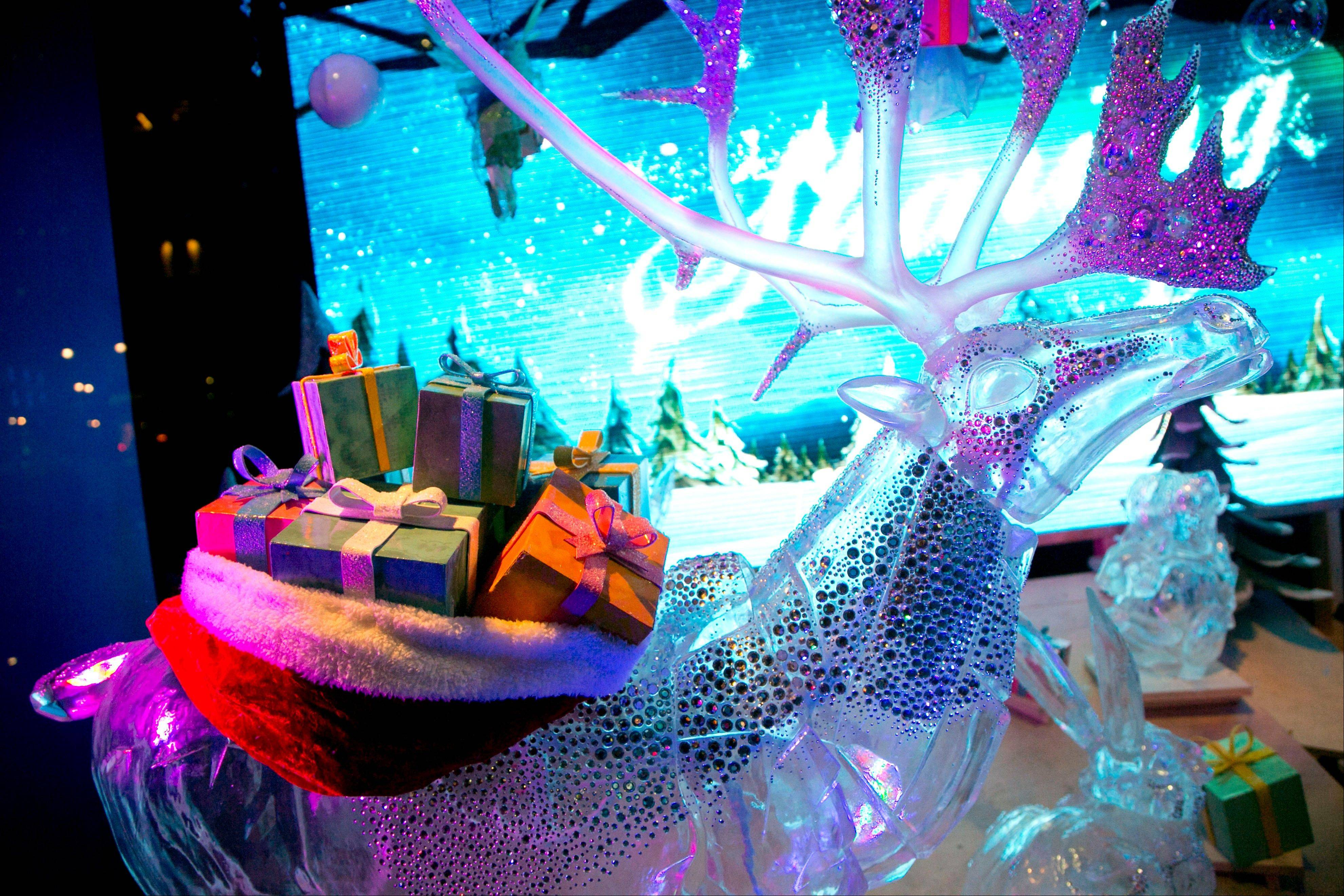 A reindeer sculpture carries a load of gift-wrapped presents in a holiday window display at Macy's in New York.