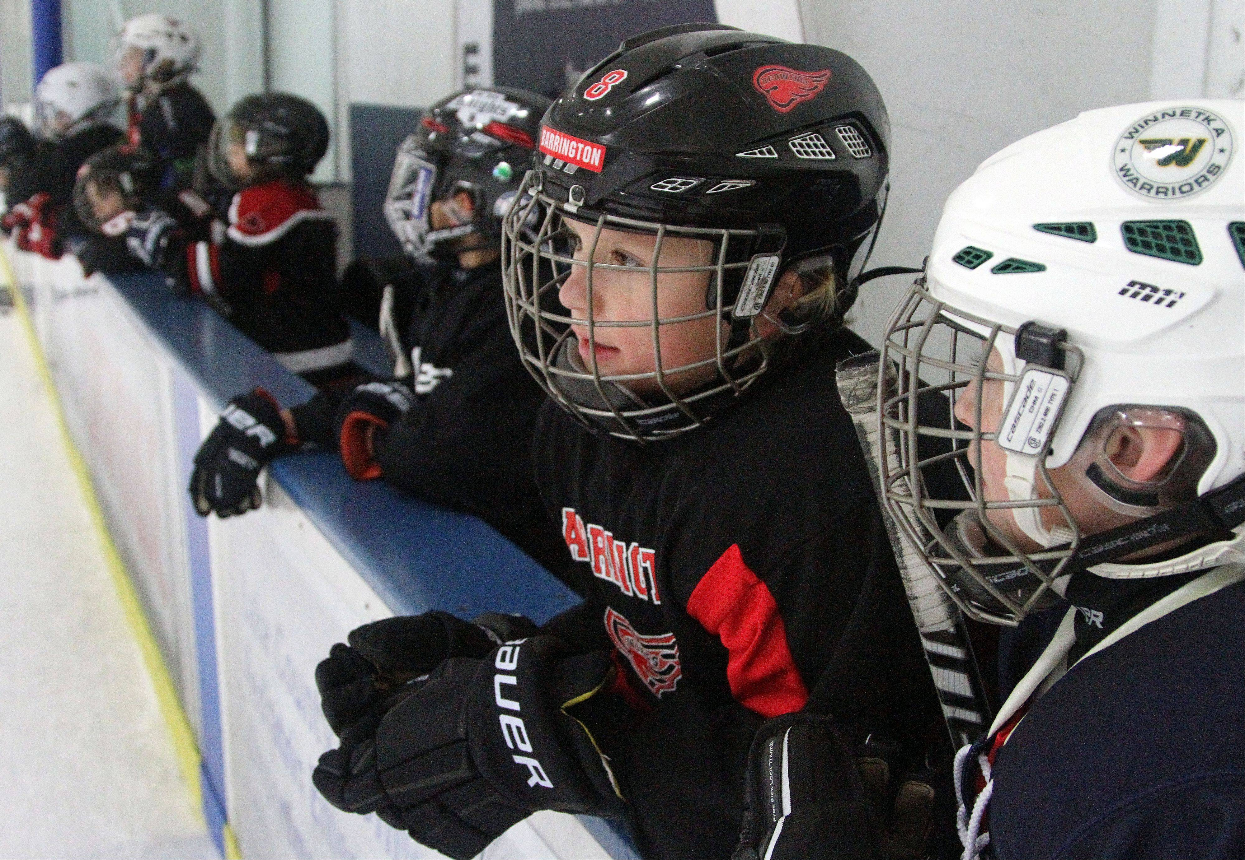 Pijus Zemaitis, 9, of Barrington, and Ben Snyderman, of Winnetka, listen to instructions from the bench as former Chicago Blackhawks player Steve Dubinsky leads a hockey clinic Wednesday at Glacier Ice Arena in Vernon Hills.