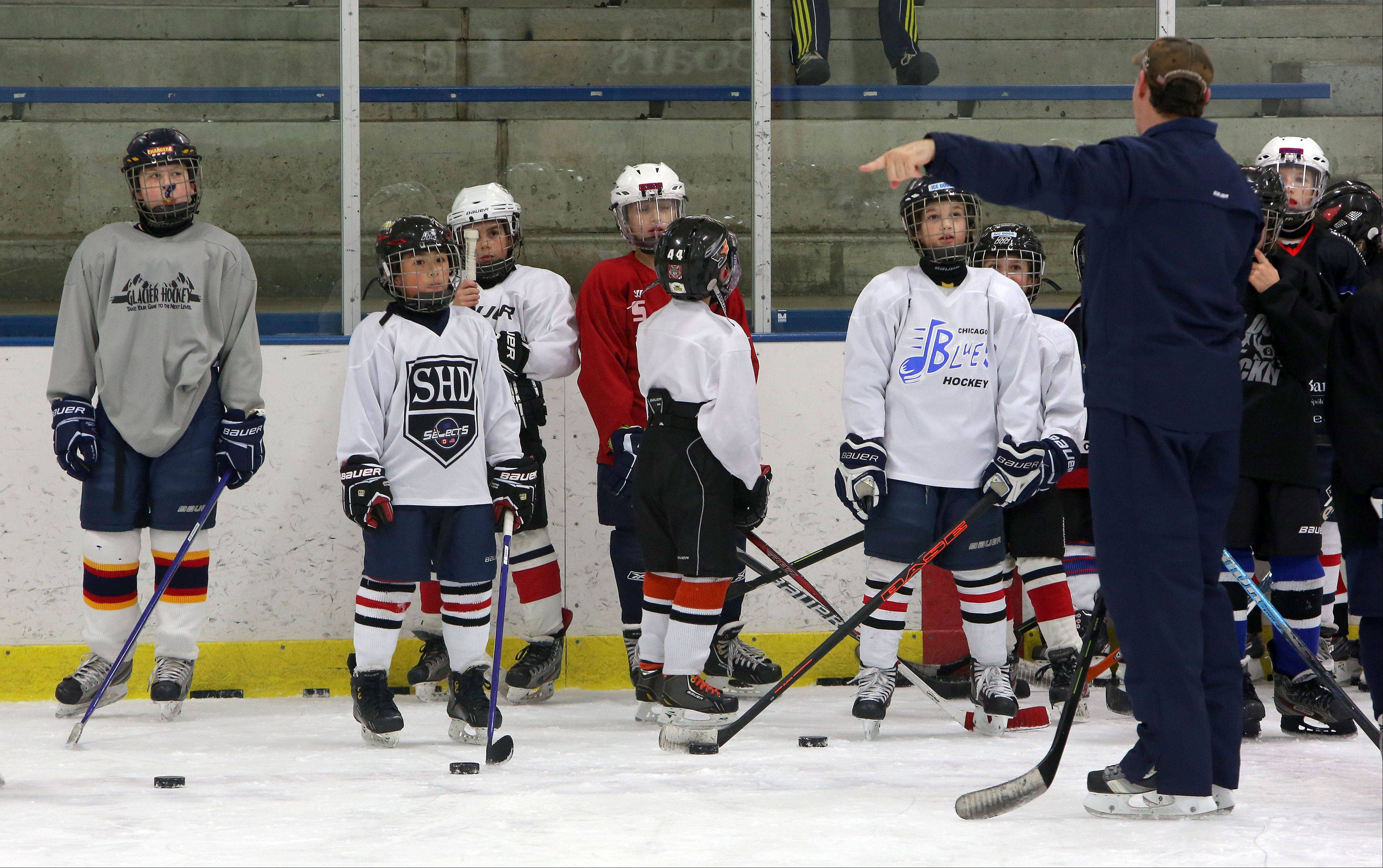 Former Chicago Blackhawks player Steve Dubinsky talks to kids Wednesday during his hockey clinic at Glacier Ice Arena Wednesday in Vernon Hills.