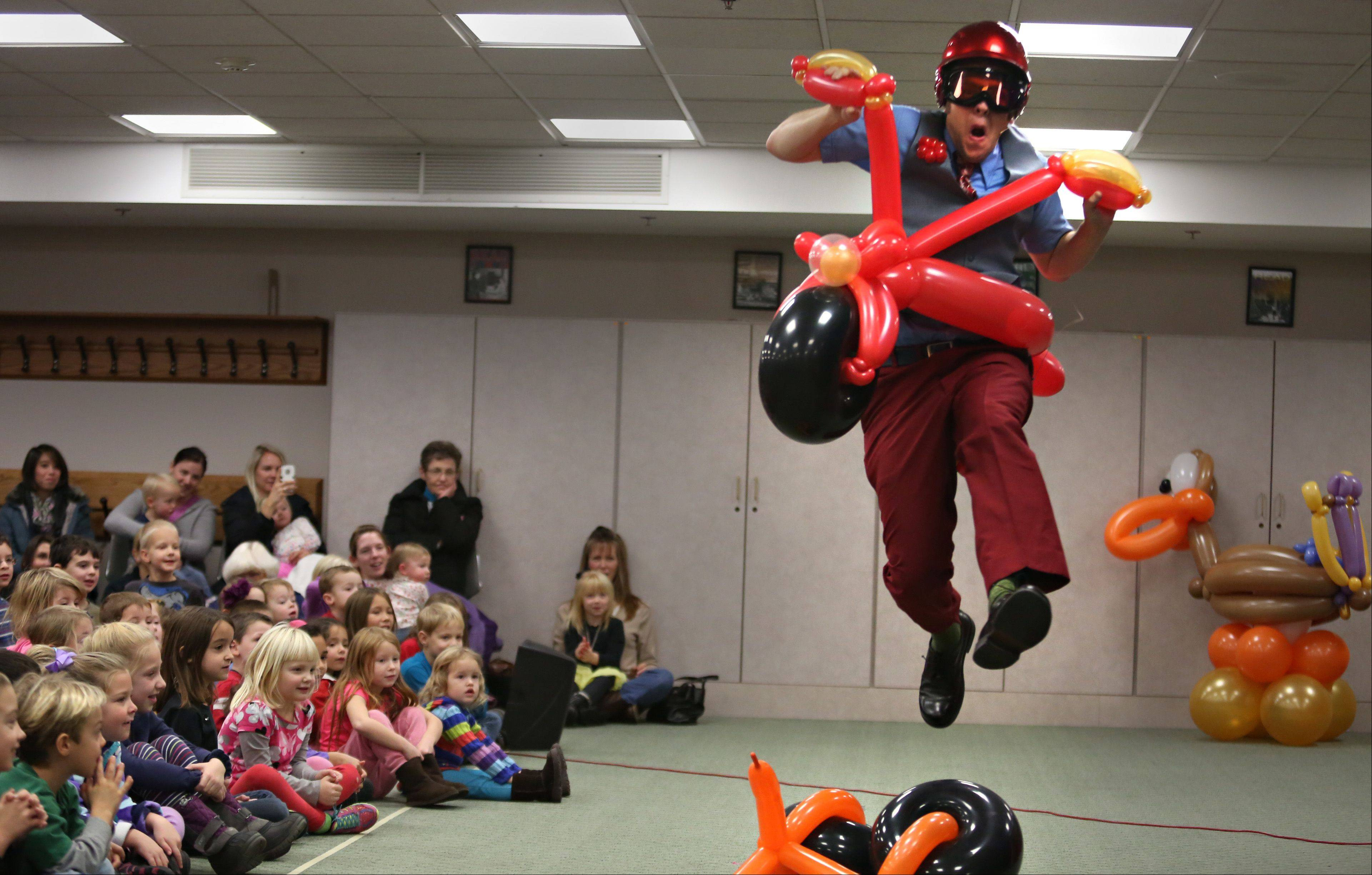 "Smarty Pants uses his balloon motorcycle to jump a balloon bicycle Tuesday during ""The Smarty Pants Big Balloon Show"" at the Geneva Public Library."
