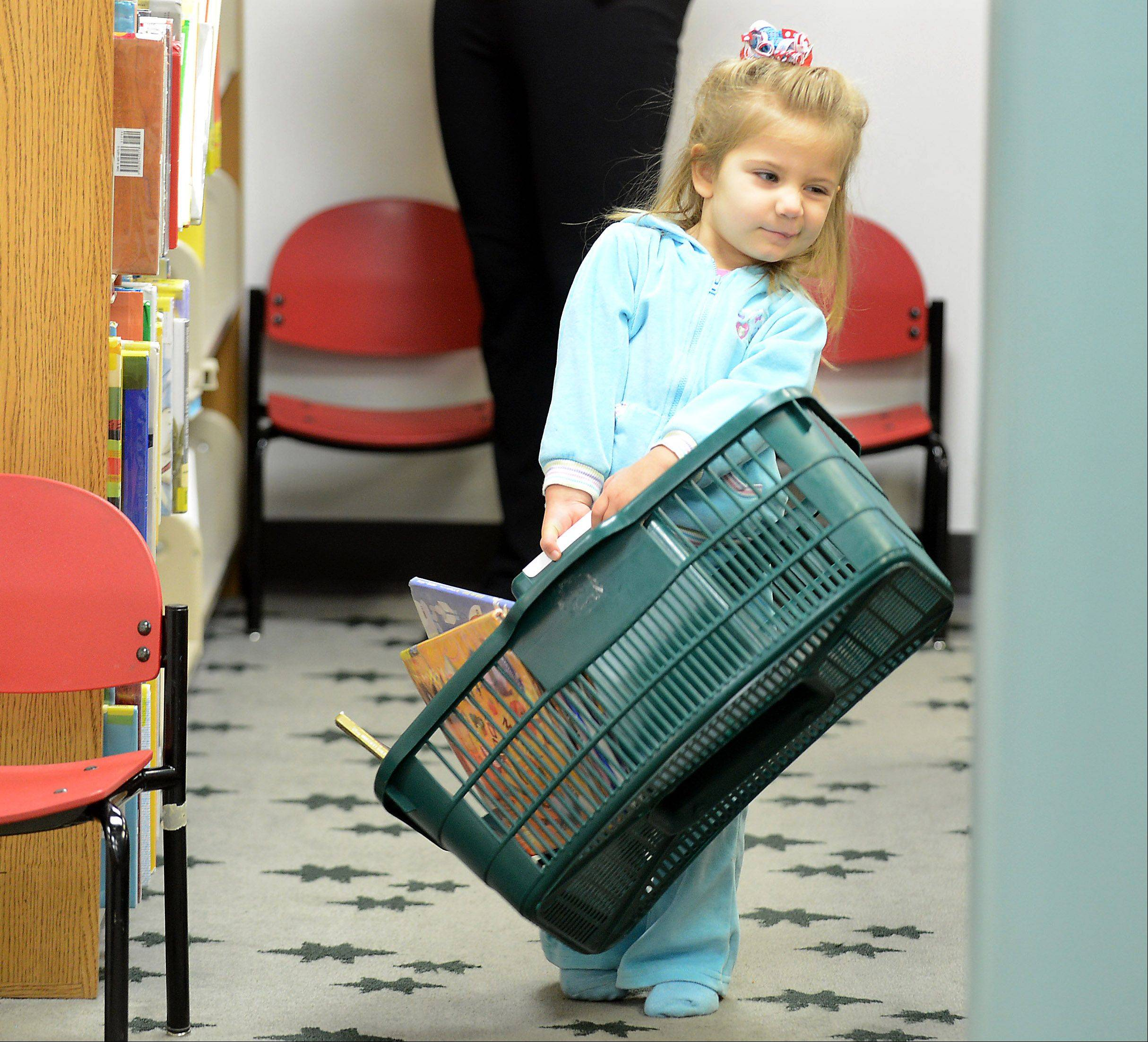 Genevive Sroufek, 3, of Geneva struggles to tote a basket of books while looking for things to check out Monday at the Geneva Public Library. Her mom told her she could get three books and she had it whittled down to 12 at the time.