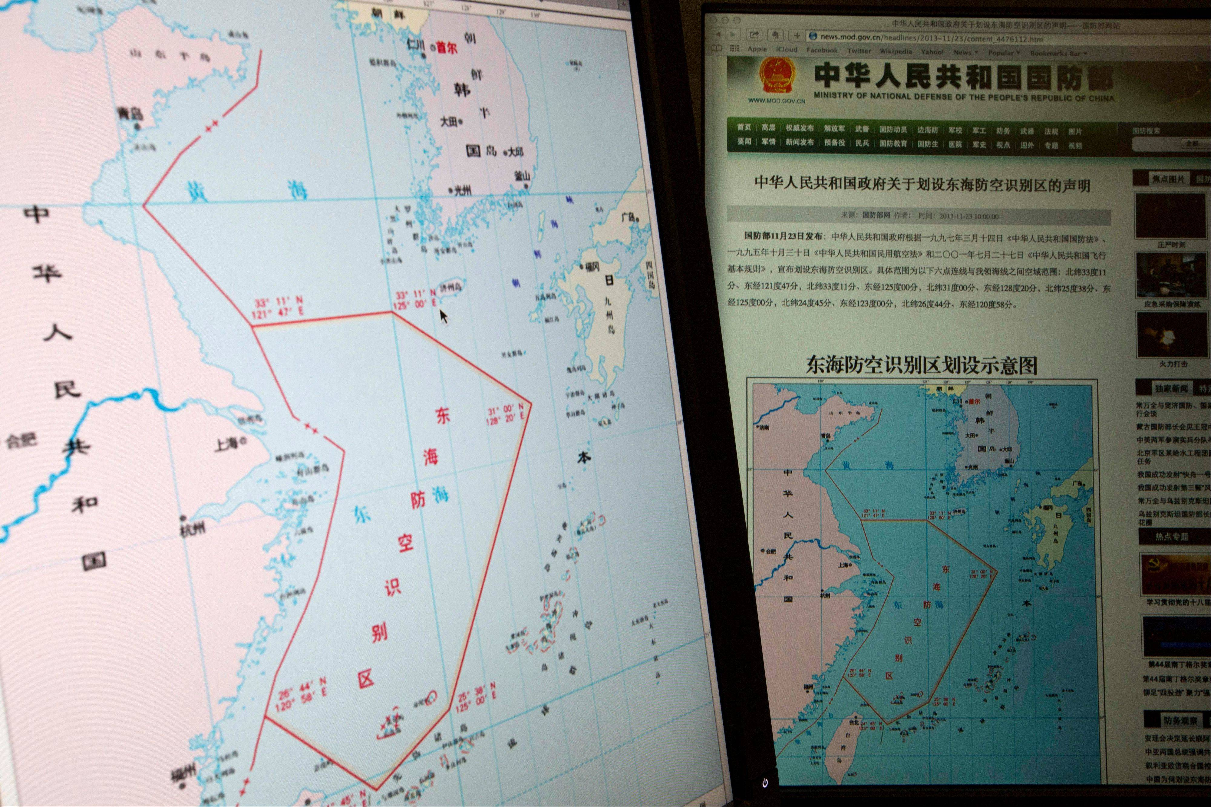 "Computer screens display a map showing the outline of China's new air defense zone in the East China on the website of the Chinese Ministry of Defense, in Beijing Tuesday, Nov. 26, 2013. Beijing on Saturday, Nov. 23, 2013 issued a map of the zone - which includes a cluster of islands controlled by Japan but also claimed by China - and a set of rules that say all aircraft entering the area must notify Chinese authorities and are subject to emergency military measures if they do not identify themselves or obey Beijing's orders. Chinese characters in red in the center of the map at left reads: ""Air Defense Identification Zone in East China Sea."""