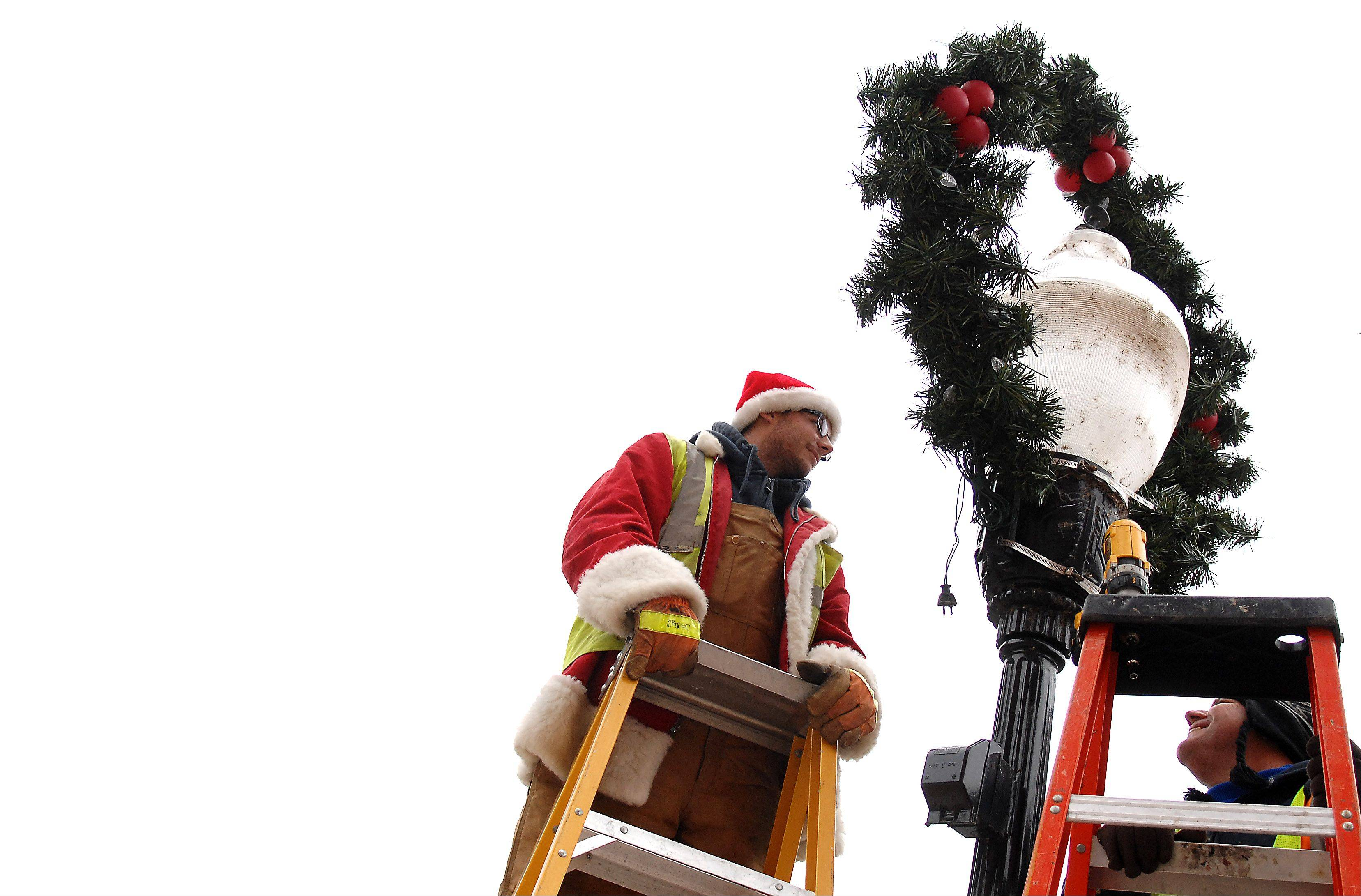 Village of Algonquin public works employee Matthew Seveska, dressed in a leftover Santa coat and hat, and Mike Schaffter put up wreaths Tuesday morning throughout the downtown area. They're decorating 18 light poles total with wreaths, garland and bows.