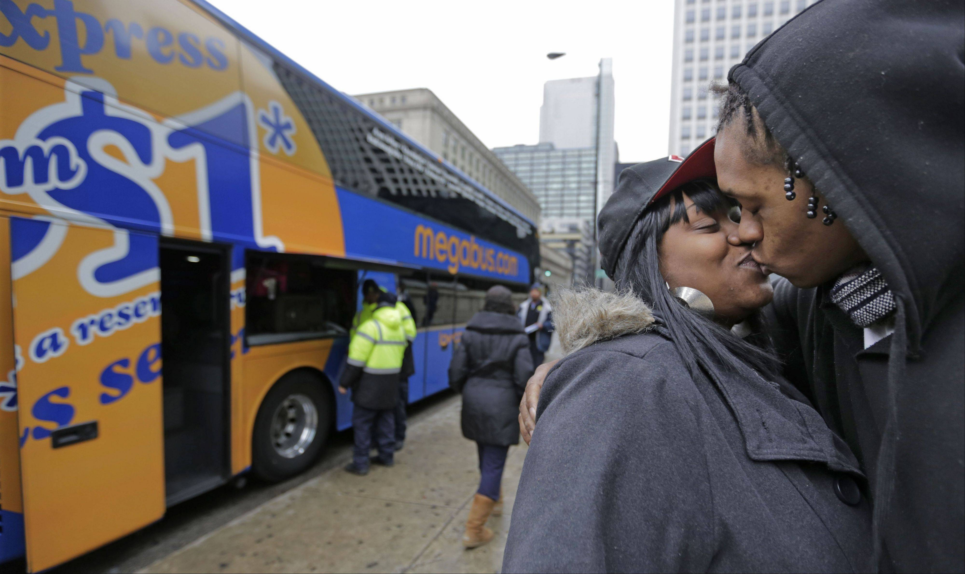 Shay Owens kisses her boyfriend Bryan Jordan before boarding a Megabus for a trip to Atlanta, Tuesday, Nov. 26, 2013, in Chicago. Millions of Americans are hurtling along the nation's jumble of transportation arteries for Thanksgiving, and more of them are discovering that a bus, of all things, is the cheapest, comfiest and coolest way to stay Zen during the nation's largest annual human migration.