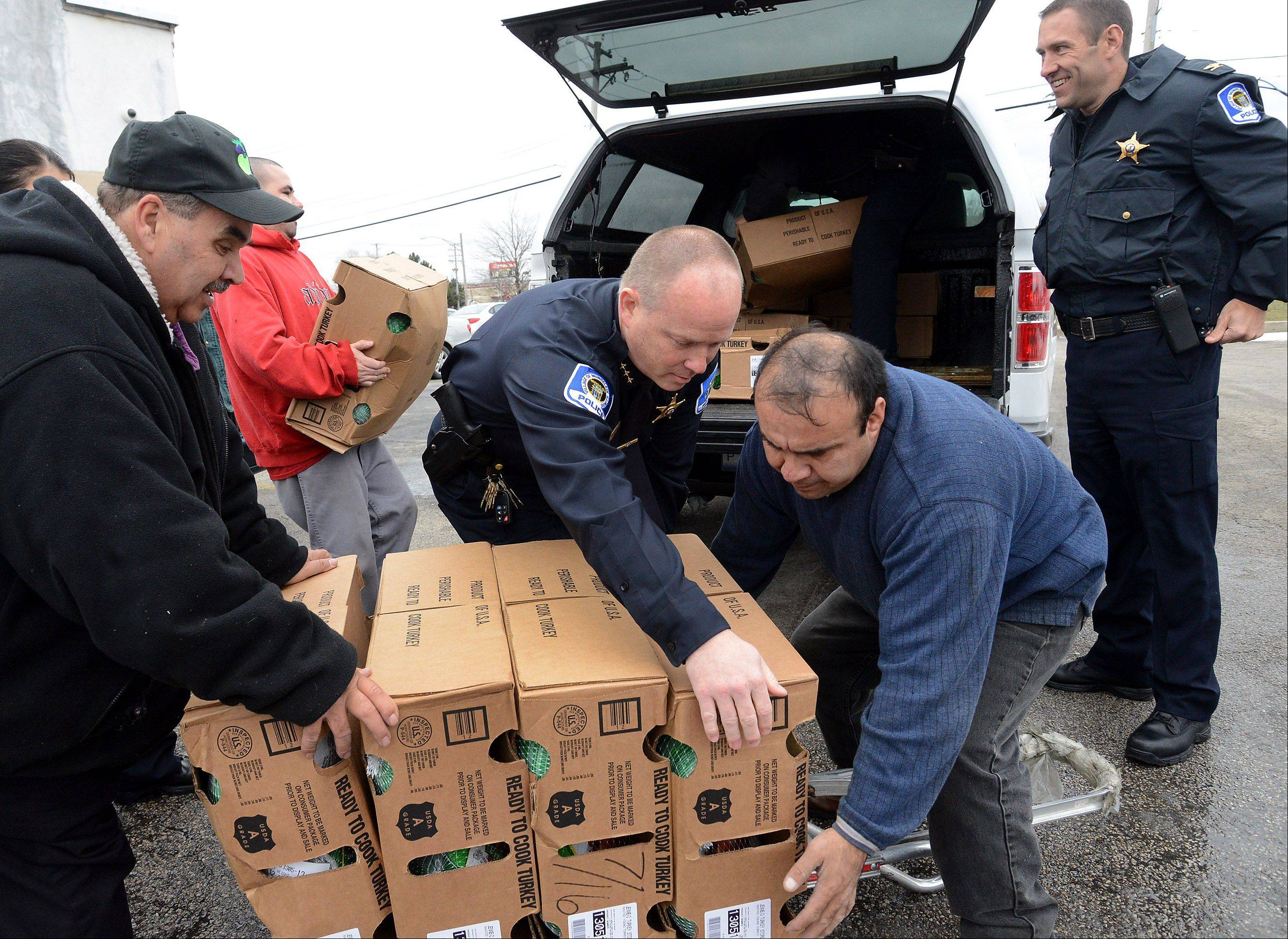 Mundelein Police Chief Eric Guenther, center, helps load up a police vehicle with turkeys on Tuesday for delivery to local families in need. This is the 13th year the Mundelein Police Department and Elly's Pancake House teamed up to provide Thanksgiving meals to needy families in the community.