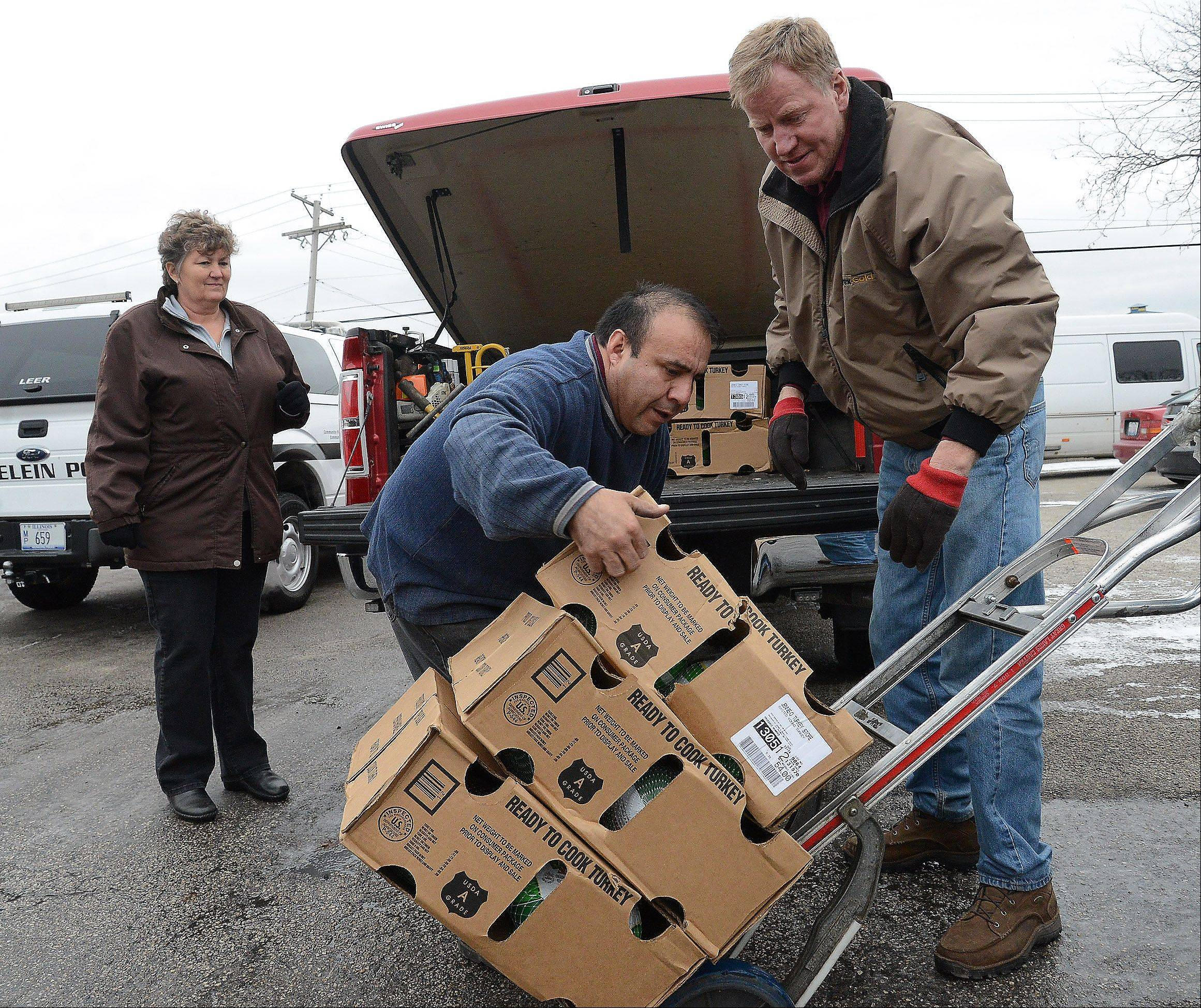 Bob Chwedyk/bchwedyk@dailyherald.comFremont Township Highway Commissioner Bill Grinnell, right, is helped by Jose Mendoza of Elly's Pancake House to load turkeys into his vehicle for the Fremont Township Food Pantry. Fremont Township joined the Mundelein Police Department and Elly's on Tuesday to provide Thanksgiving meals to local families in need.