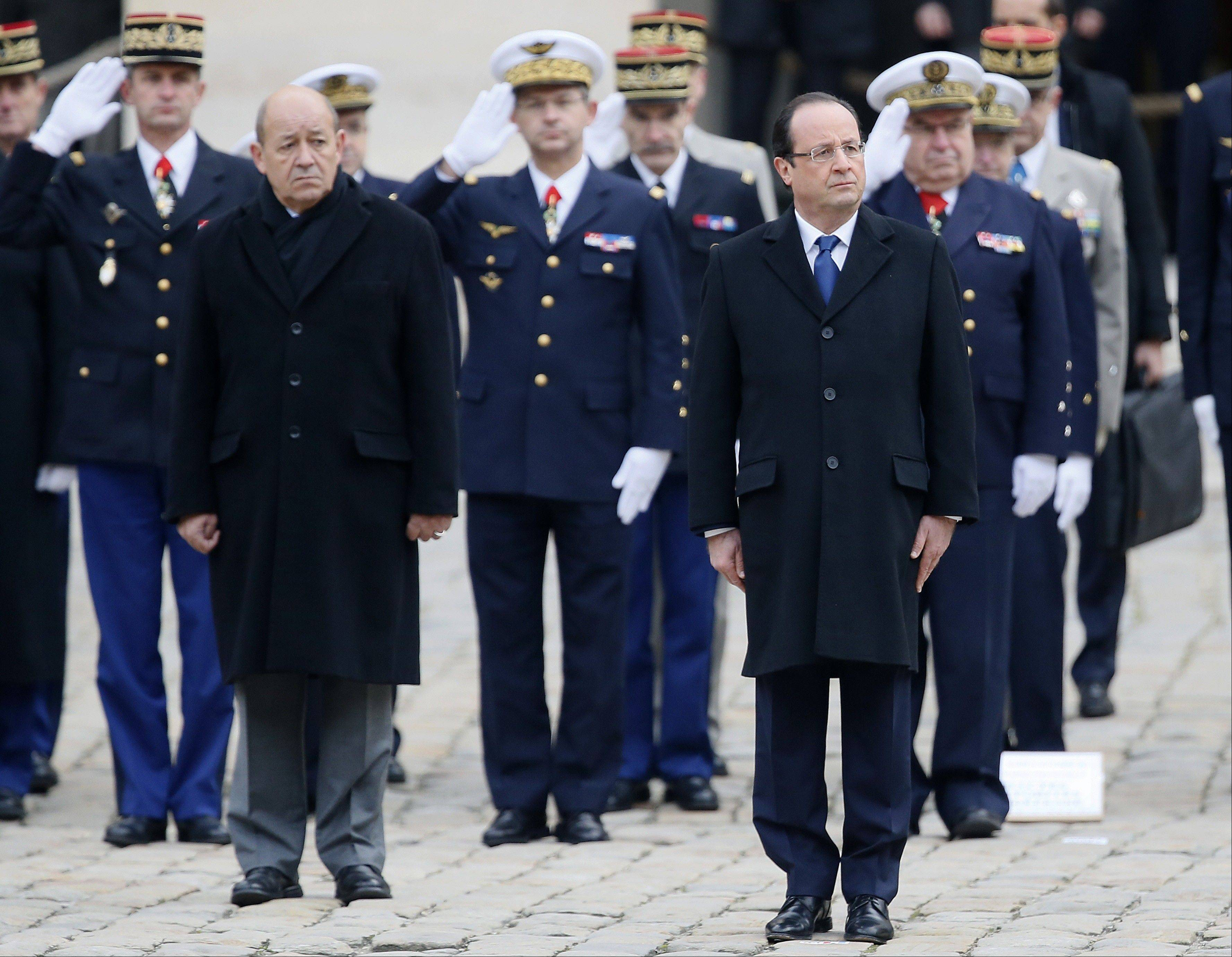 French President Francois Hollande, right, and Defense Minister Jean-Yves Le Drian reviews the troops during a military ceremony, Tuesday, Nov. 26, 2013, at the Invalides in Paris. France will send 1,000 troops to Central African Republic under an expected U.N.-backed mission to keep growing chaos at bay.