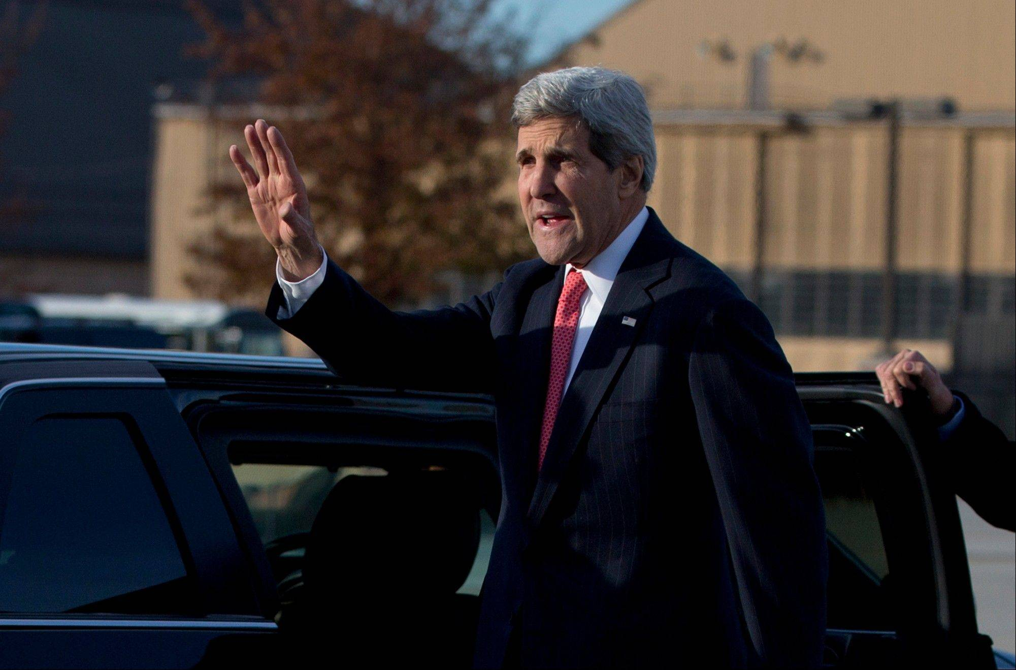 Secretary of State John Kerry waves before getting into his motorcade vehicle as he arrives at Andrews Air Force Base, Md., Monday, Nov. 25, 2013, as he returns from London. While in London Kerry had meetings with Libyan's Prime Minister Ali Zeidan and British Foreign Secretary William Hague. Prior to London, Kerry was in Geneva, Switzerland, for the Iran nuclear talks.