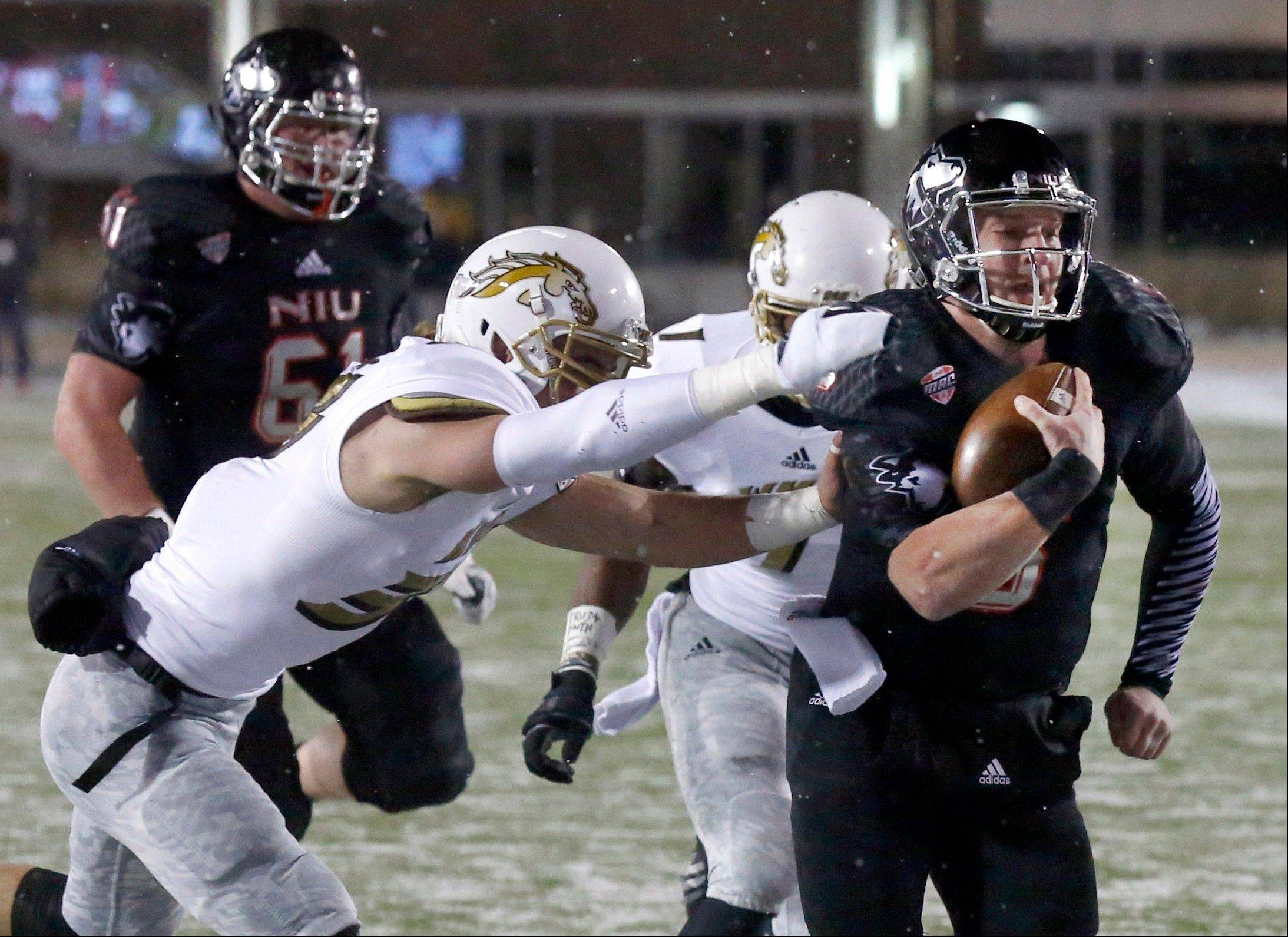 Northern Illinois quarterback Jordan Lynch carries the ball past two Western Michigan defenders during the first half Tuesday night in DeKalb.