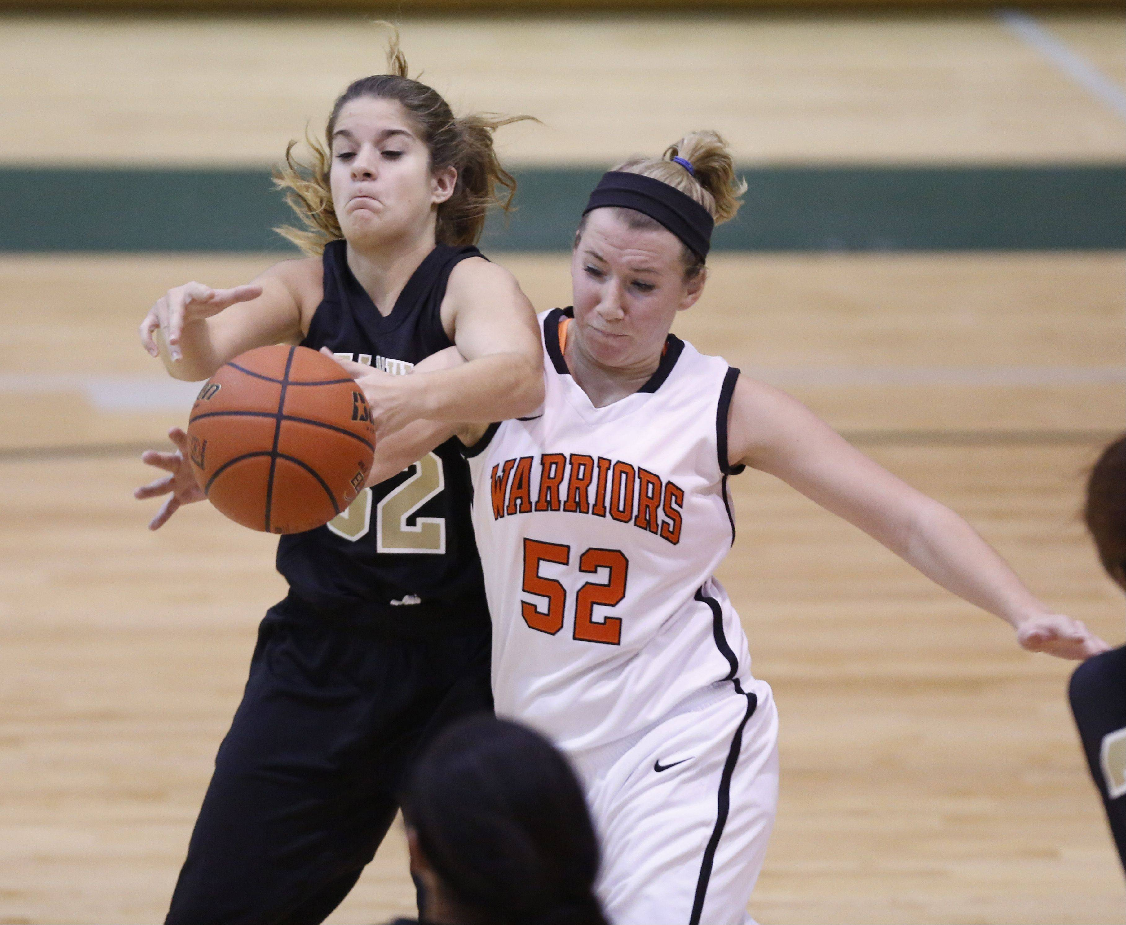 Streamwood's Rachel Clark (32) battles McHenry's Sawyer Lay (52) for a loose ball during Friday's basketball at Crystal Lake South.