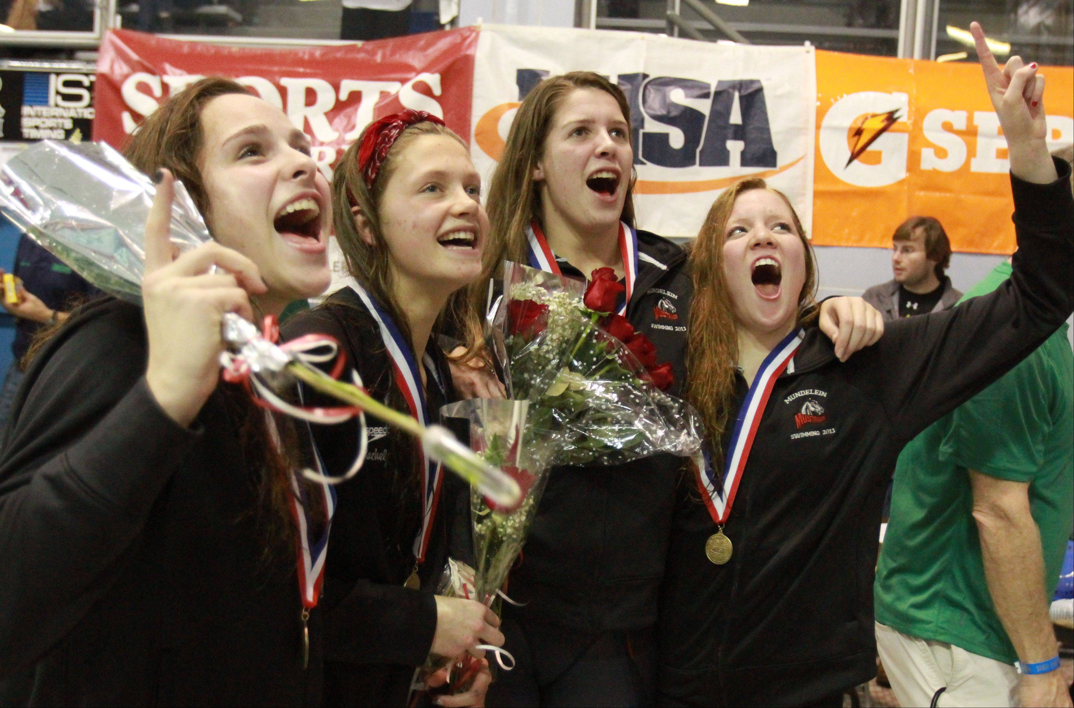 Mundelein's 200-yard freestyle relay team, Erin Falconer, Jennifer Kordik, Rachel Robb and Karrie Kozokar celebrate their first-place finish at Saturday's state swimming finals.