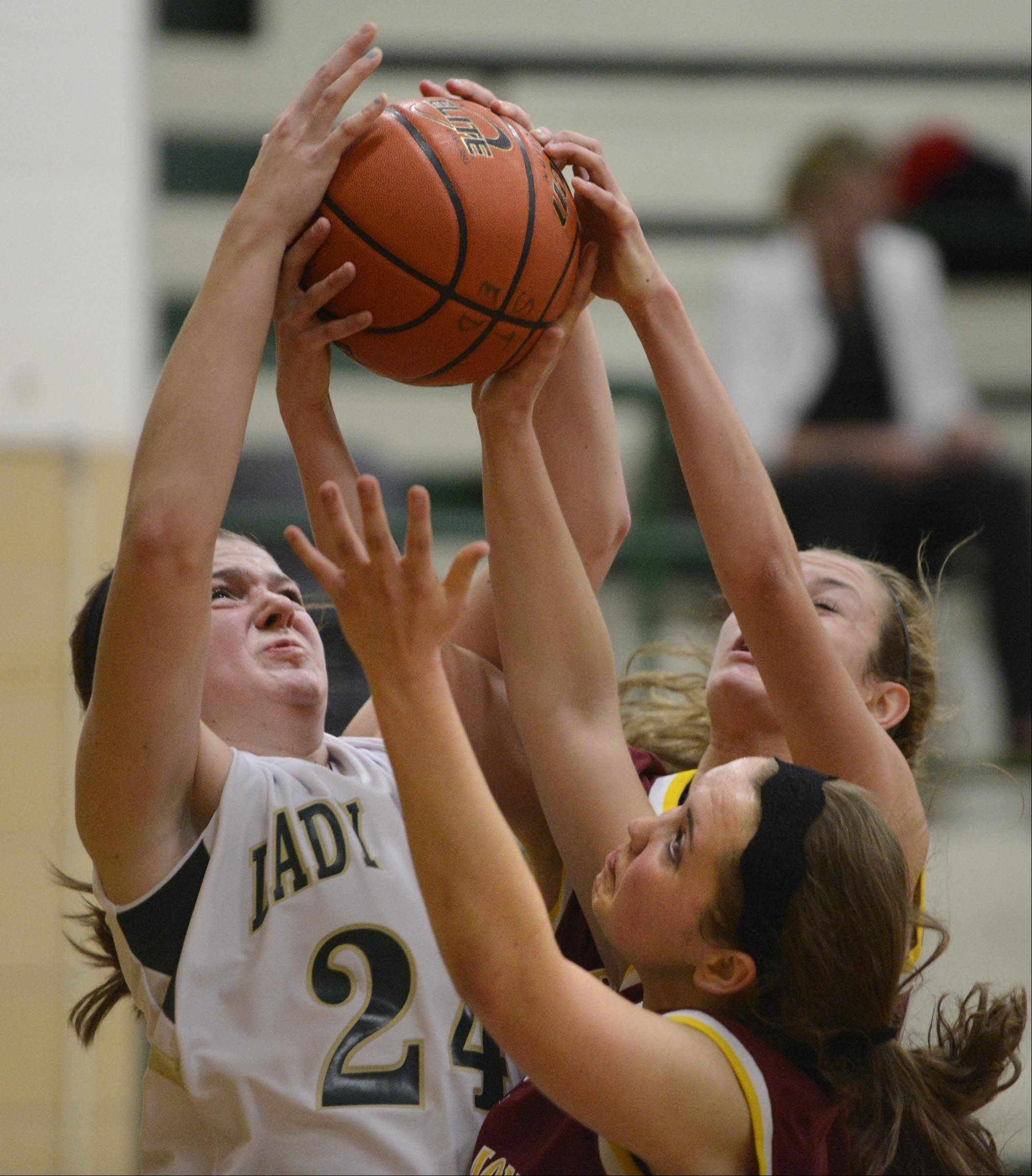 St. Edward's Katie Swanson fights for a rebound against Westmont's Rachel Kirt and Annie Carlon Tuesday in Elgin.