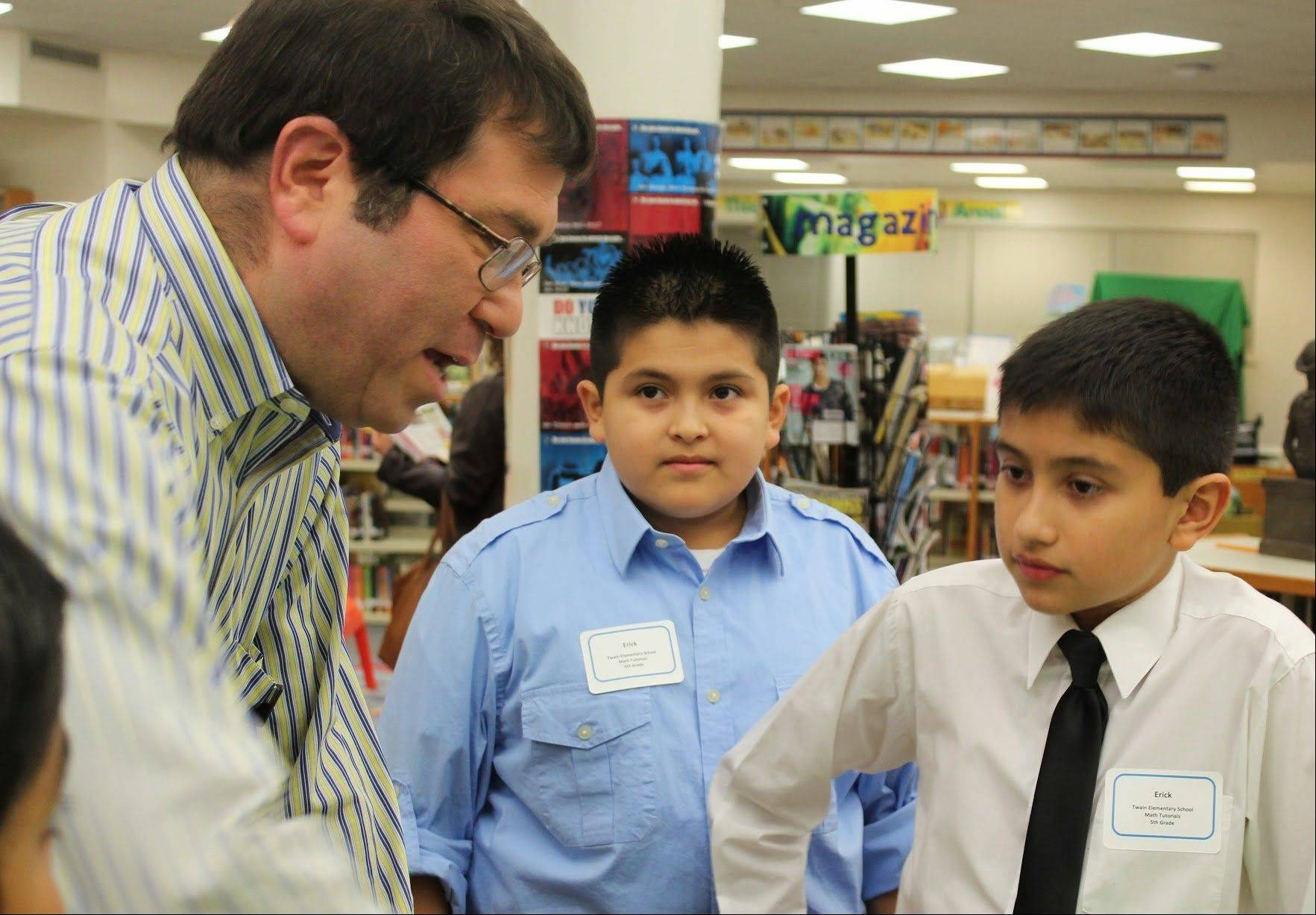 Fifth-graders Erick Garduno, center, and Erick Miranda, right, field a question from District 21 board President Bill Harrison. Garduno and Miranda, students at Twain School in Wheeling, presented their math tutorial videos, which they created to help peers learn multi-digit operations.