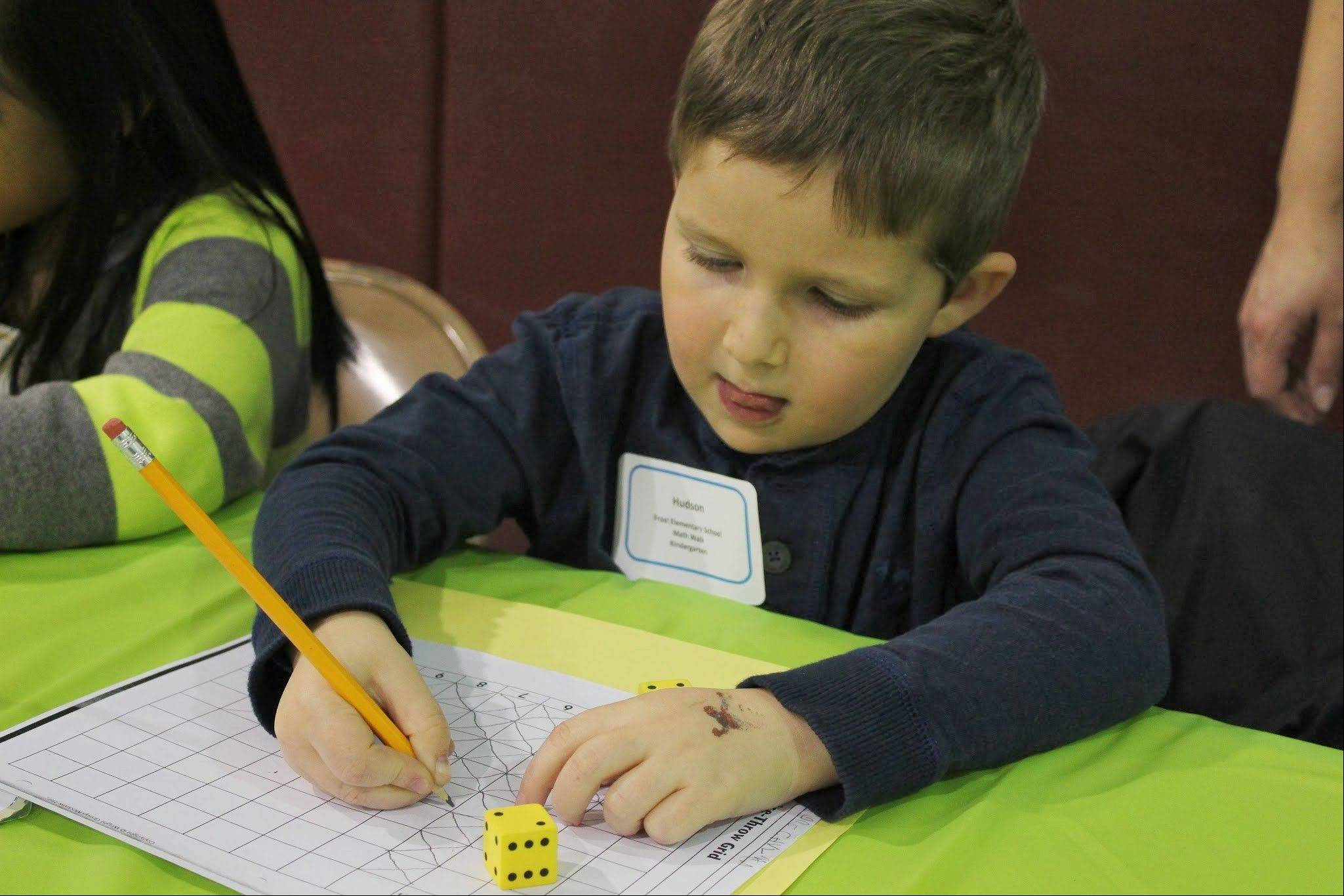 Hudson Schulman, a kindergartner from Frost Elementary School in Mount Prospect, demonstrates a math counting game at the State of the Schools event. Prekindergarten through eighth-grade students in District 21 explained to parents and community members what they are learning in school and how it connects to the world around them.