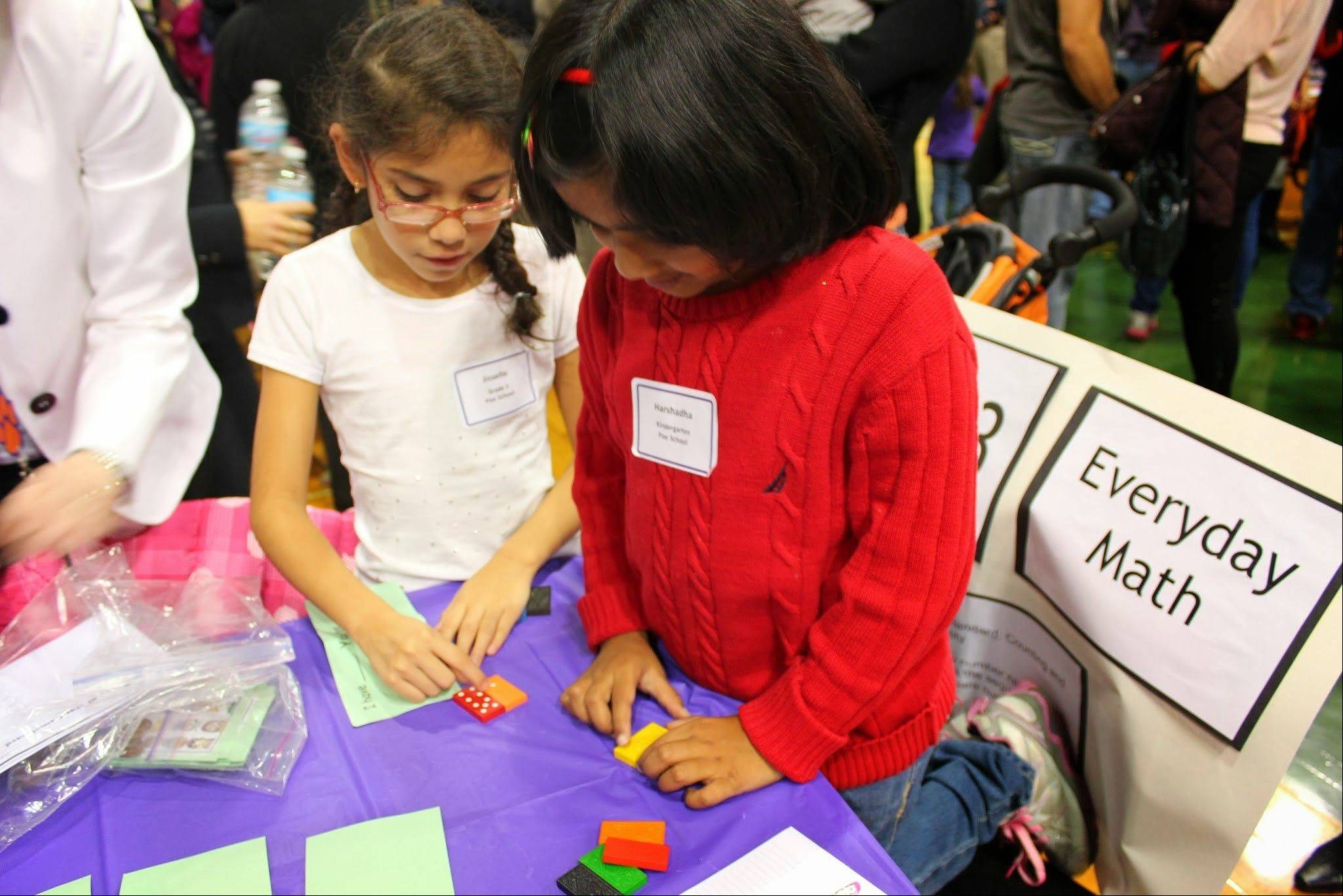 Third-grader Jisselle Gonzalez and kindergartner Harshadha Chaganti, both of Poe Elementary School in Arlington Heights, work together on a math game at District 21's annual State of the Schools event. Hundreds of people learned from students about their daily life in school.