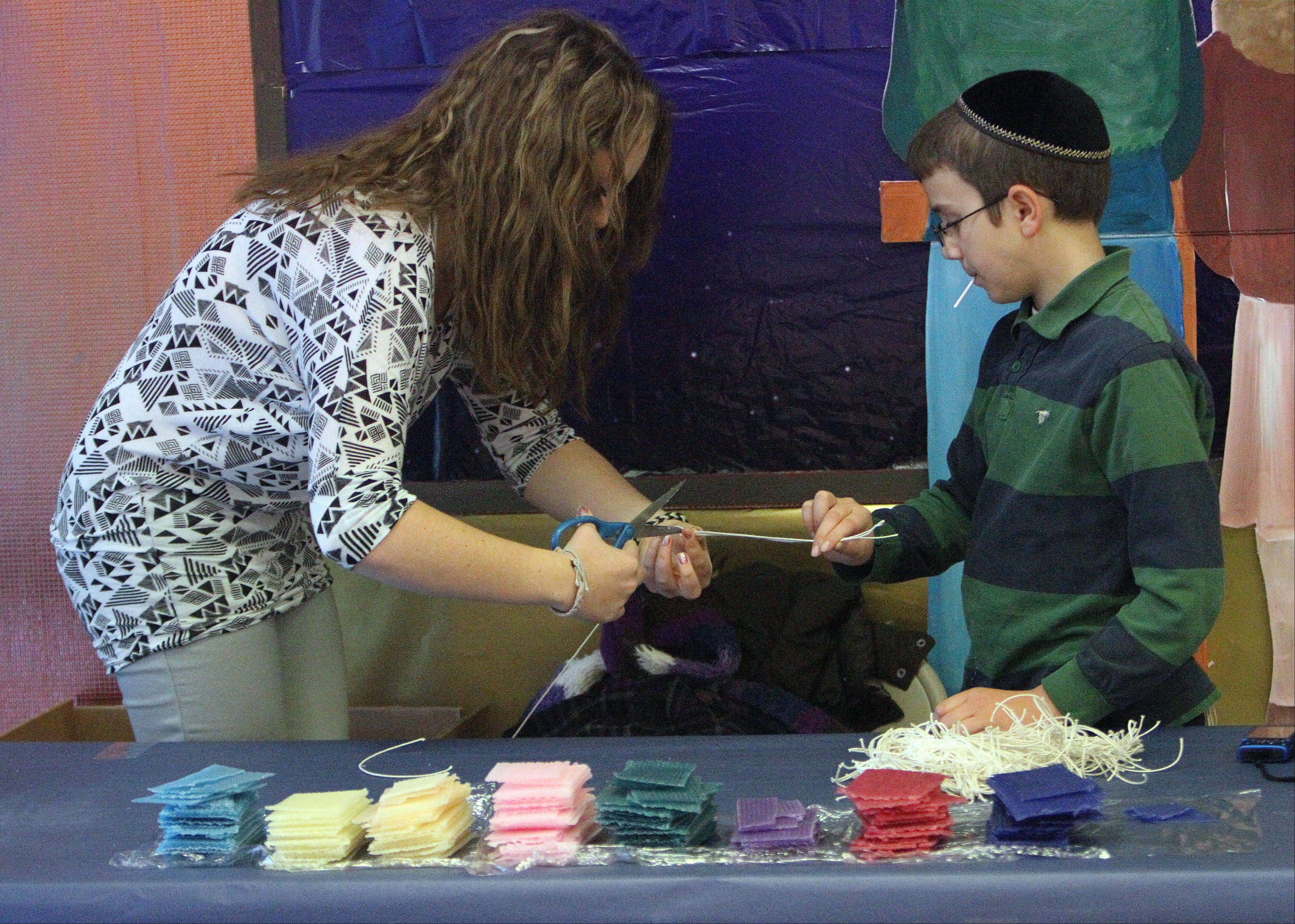 Julia Gartsman helps 11-year-old Joseph Zehnwirth make a candle Wednesday at Chanukah Family Funland in the Buffalo Grove Town Center in Buffalo Grove. Crafts, activities and entertainment continue through Sunday.