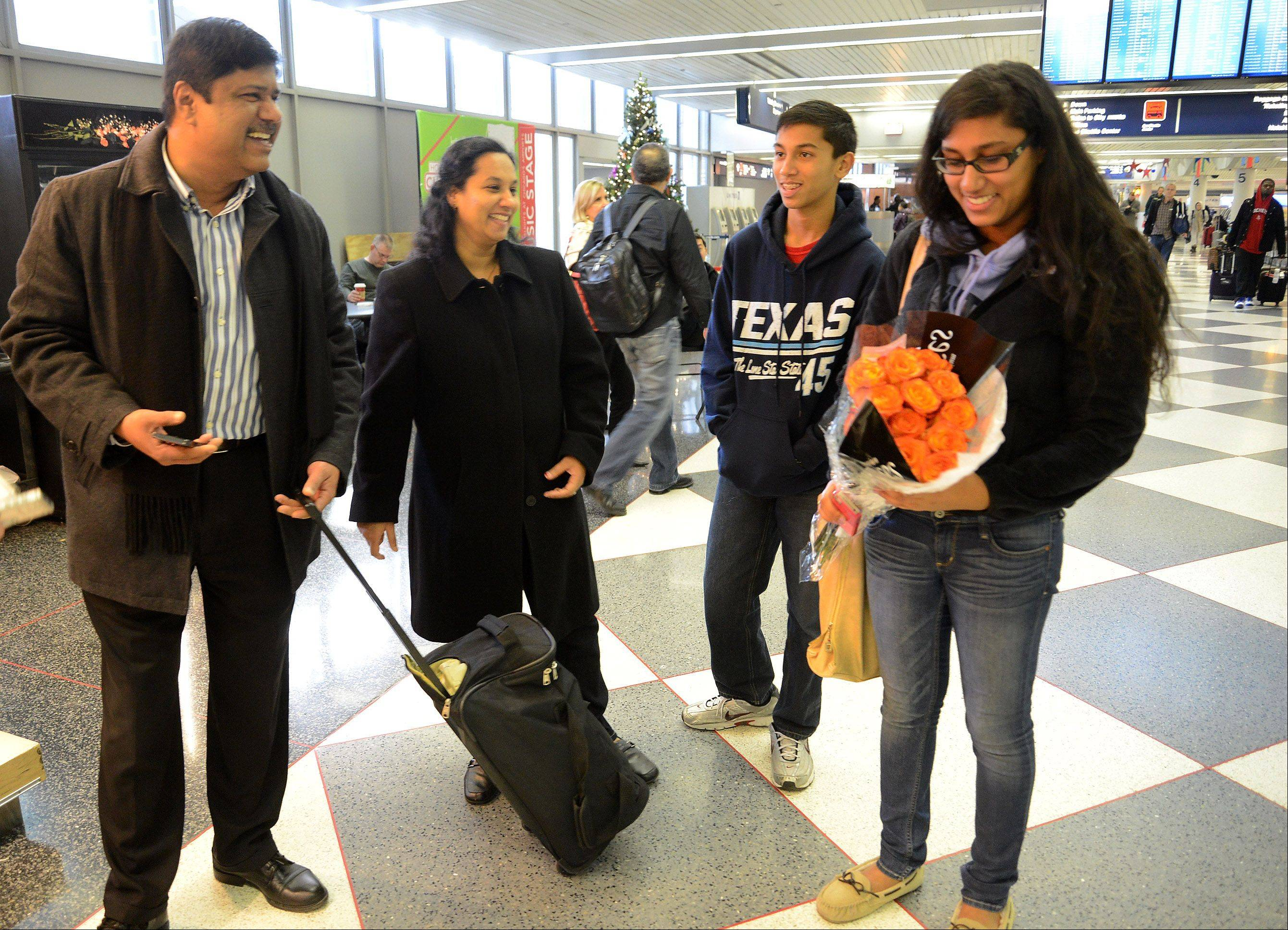 Sanjana Bendi of Palatine, a student at the University of Pittsburgh, is greeted with a bouquet by her father, Bose Bendi, mother Shanthi and brother Vijay after arriving at O'Hare International Airport.