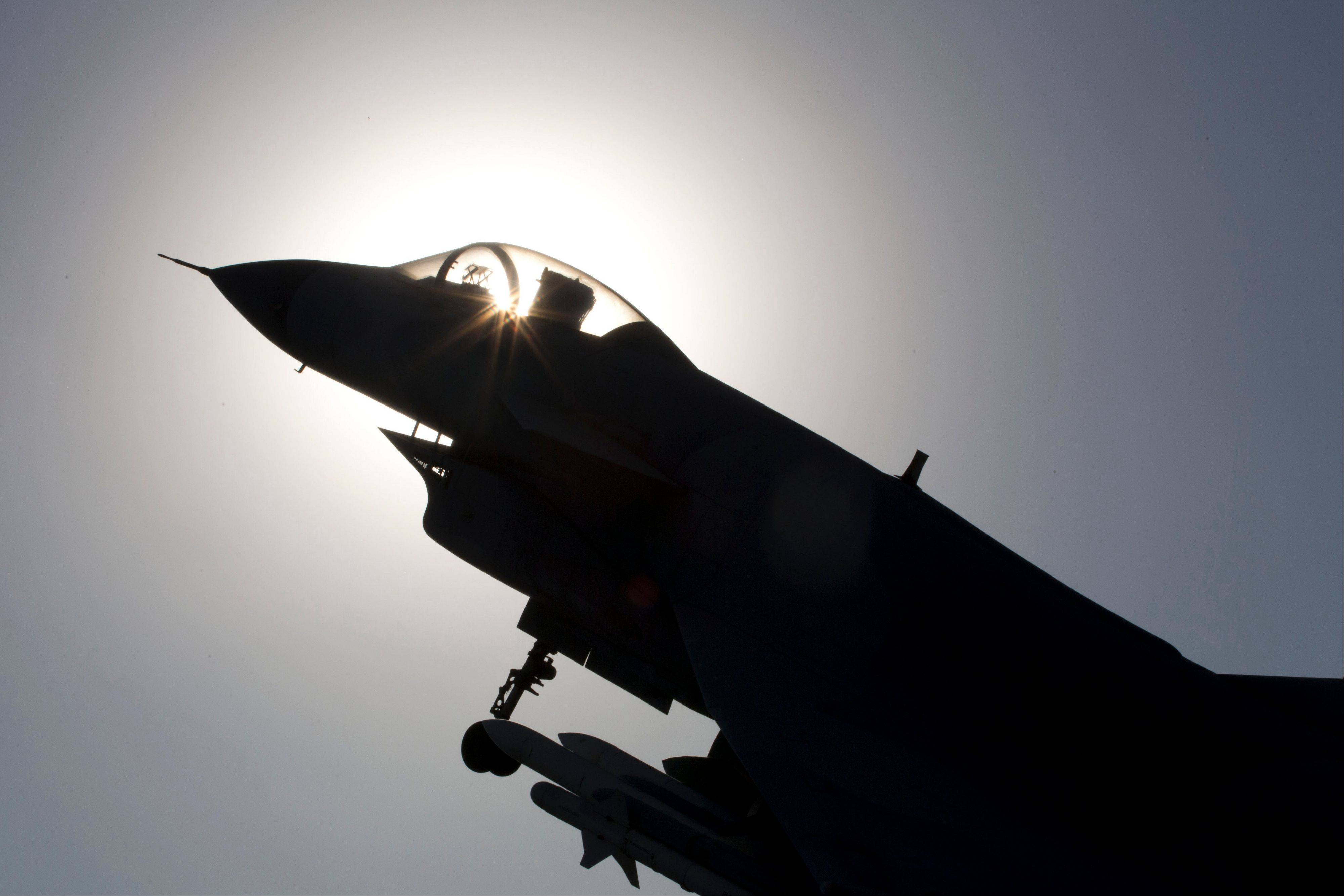 The replica of a Chinese made fighter jet is silhouetted against the sun in Beijing, China, Wednesday, Nov. 27, 2013. China said Wednesday it had monitored two unarmed U.S. bombers that flew over the East China Sea in defiance of Beijing�s declaration it was exercising greater military control over the area.