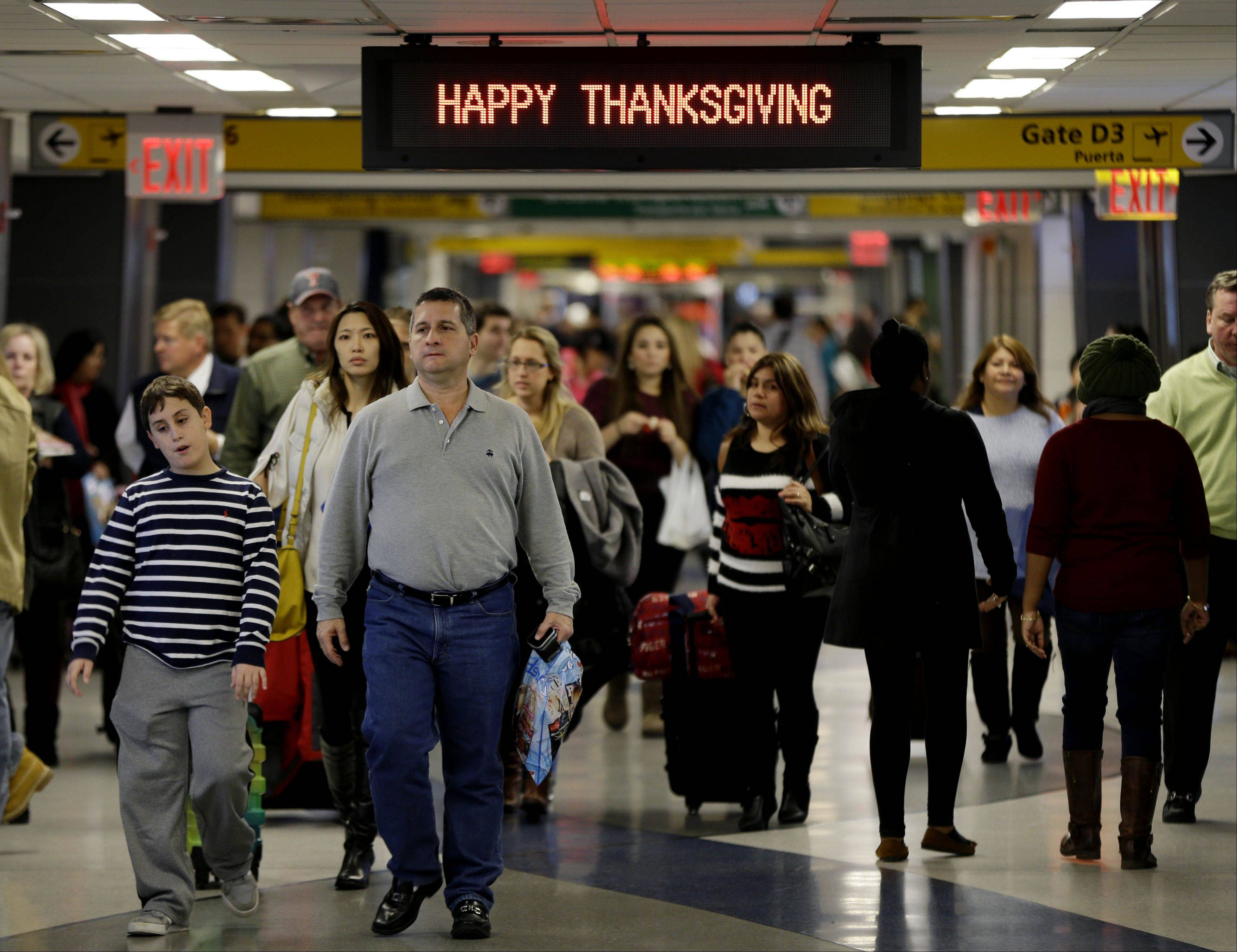 Travelers walk under a sign reading �Happy Thanksgiving� at LaGuardia Airport in New York, Tuesday, Nov. 26, 2013. A winter storm system is threatening to disrupt the plans of travelers ahead of the long Thanksgiving holiday weekend.