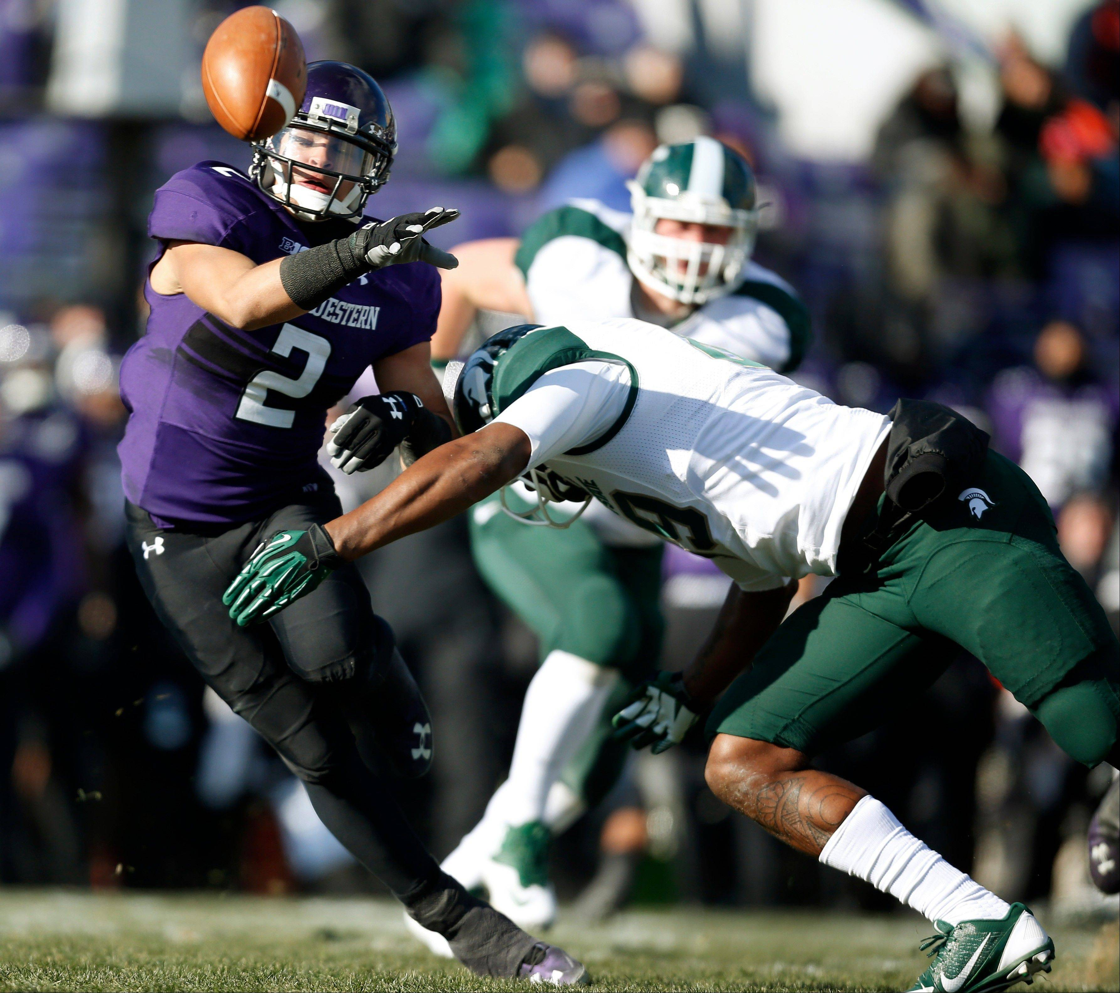 Northwestern quarterback Kain Colter takes a hit from Michigan State defensive end Shilique Calhoun during the first half of last Saturday�s game in Evanston.
