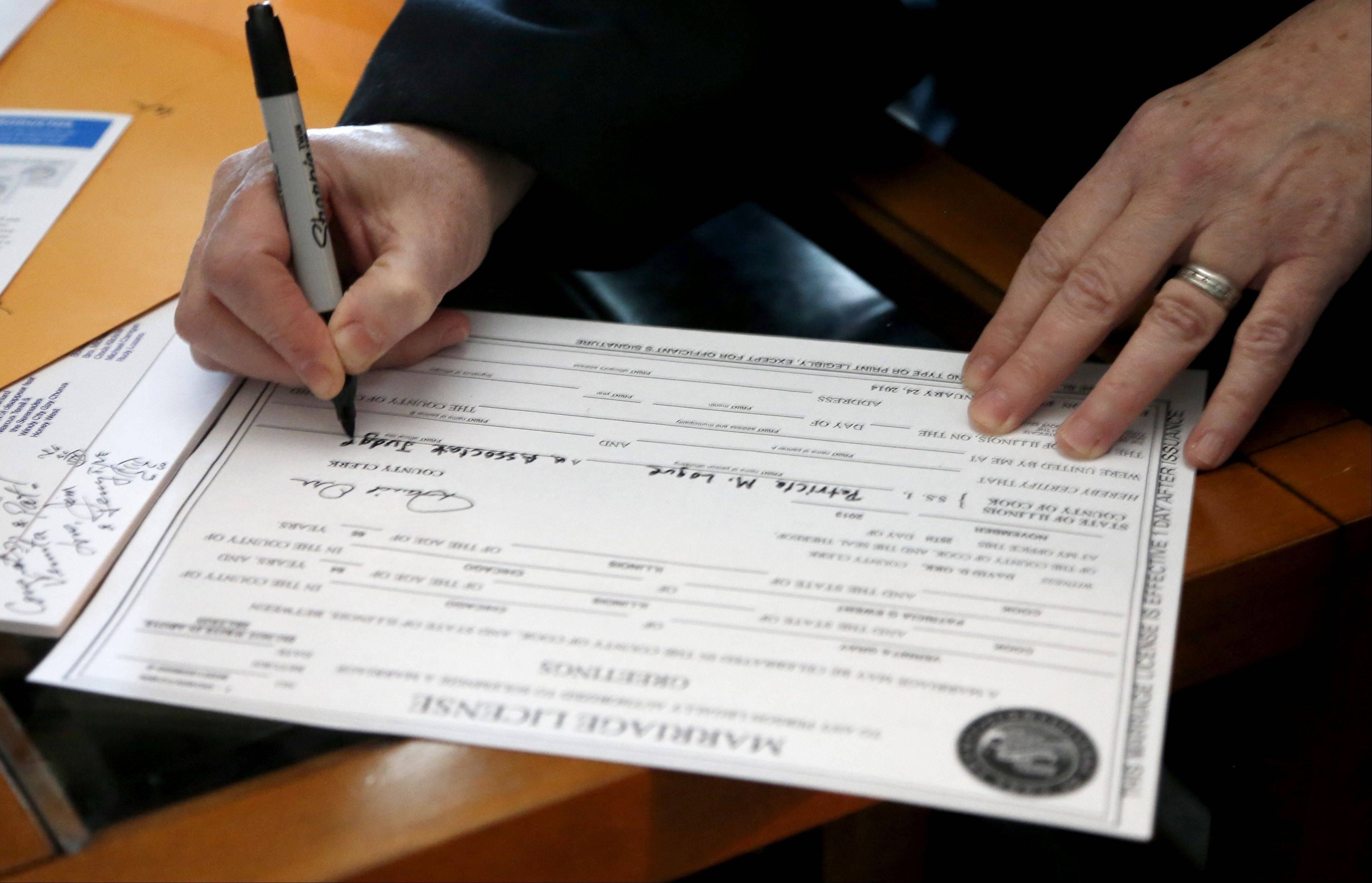 Cook County Judge Patricia Logue signs the marriage license of Vernita Gray and Patricia Ewert after their wedding ceremony on Wednesday.