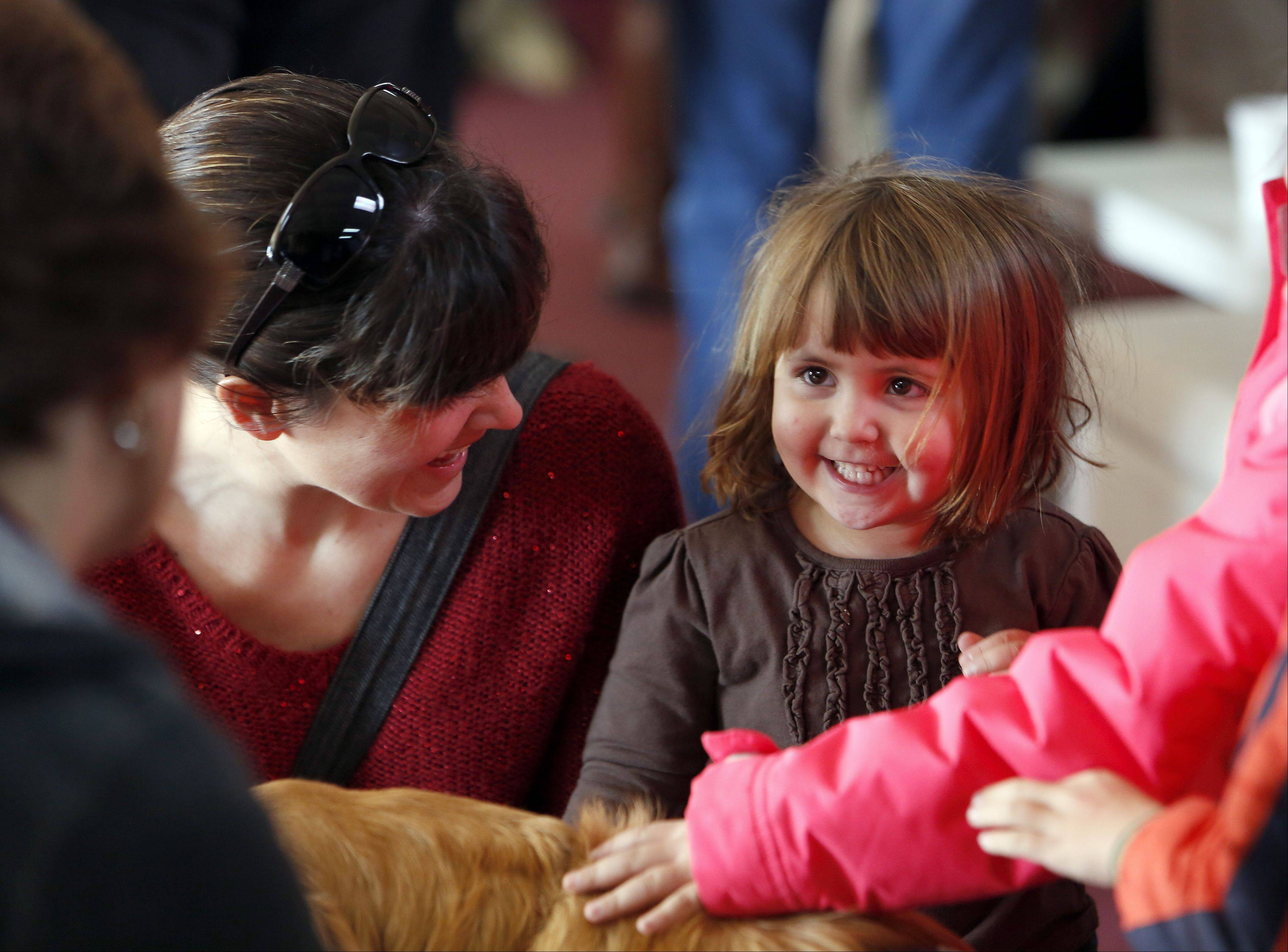 Julie and Emmi Spiezio, 2, of Washington are greeted by Chloe before services Sunday at Our Savior Lutheran Church.